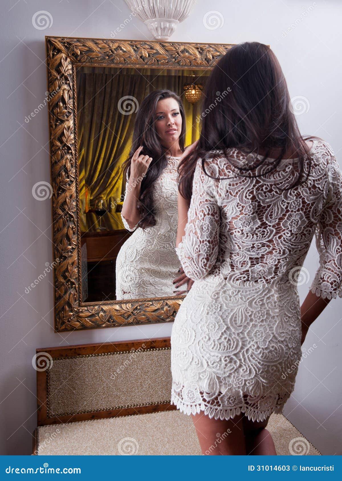 La belle fille dans une robe blanche courte regardant dans for Regard dans le miroir