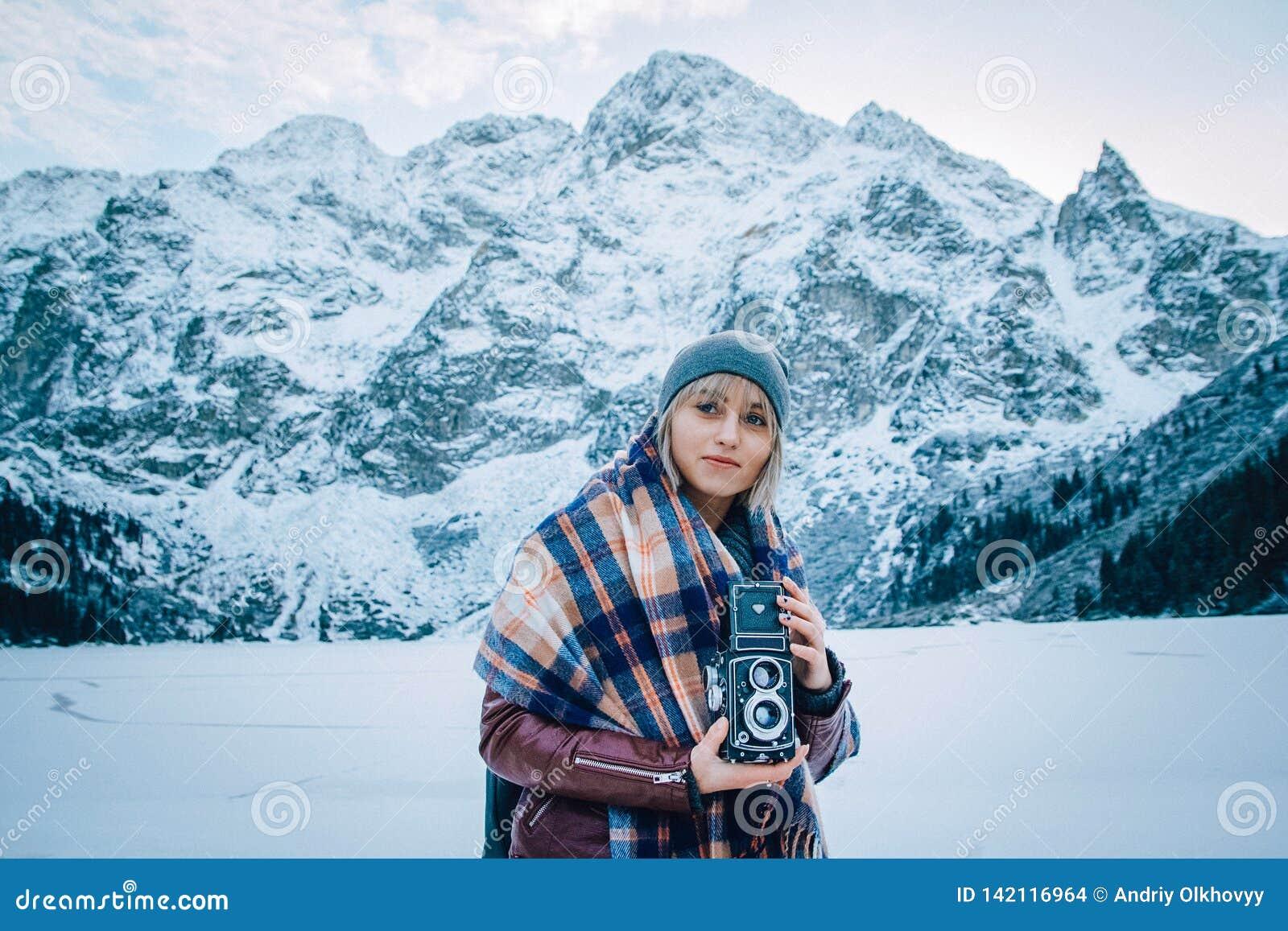 La belle fille fait une photo sur une vieille caméra de cru Dans les montagnes en hiver, risquez et voyagez