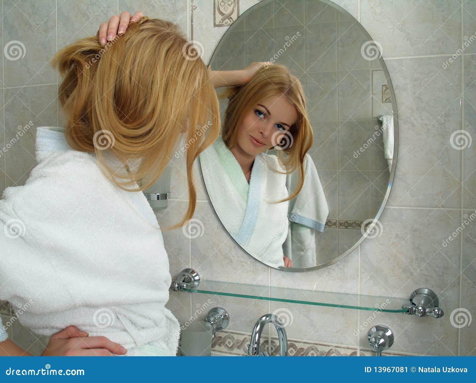 La belle fille regarde dans un miroir dans une salle de for Salle de bain fille