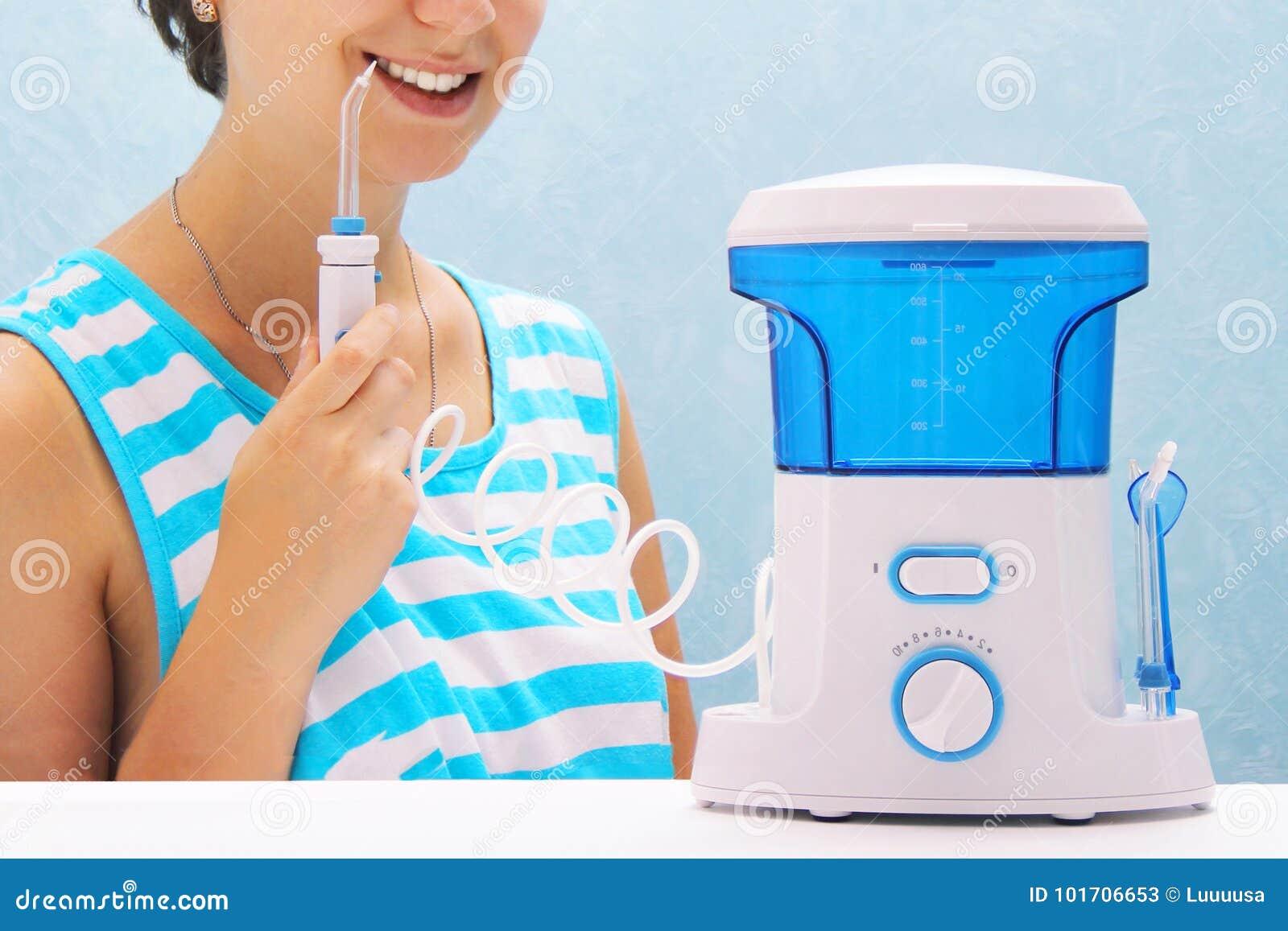 La belle fille rince ses dents avec un irrigator oral la femme sourit et tient la poignée d irrigator nettoyage des dents au hom