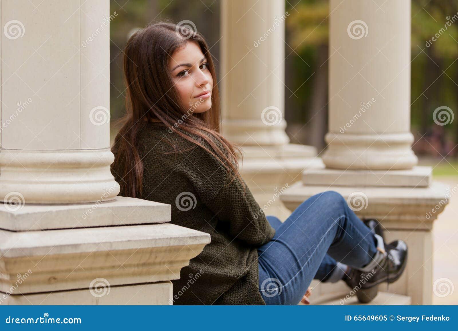 La belle fille sur une balustrade de tonnelle