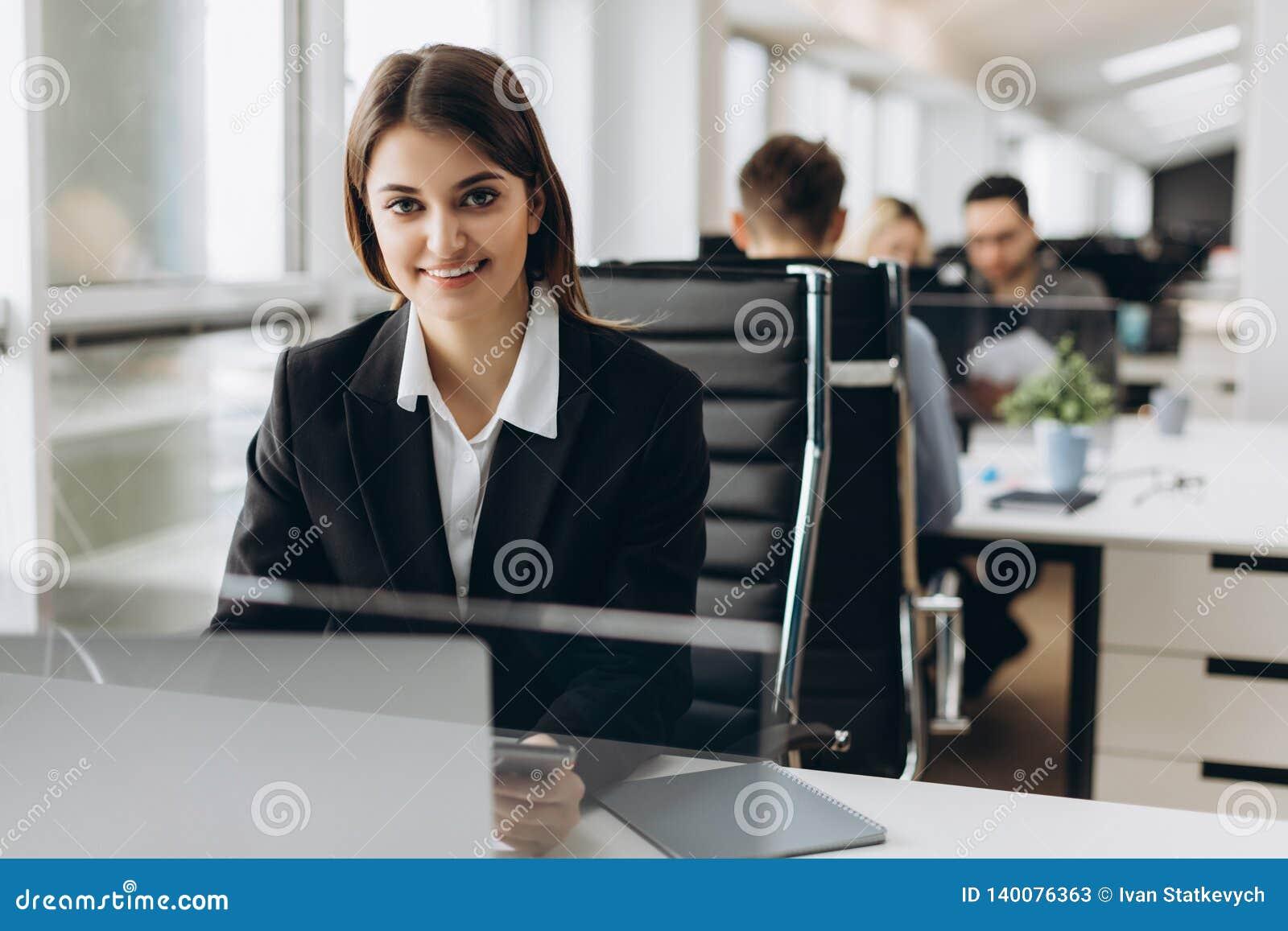 La belle jeune et réussie fille de sourire s assied à la table dans son bureau Femme d affaires