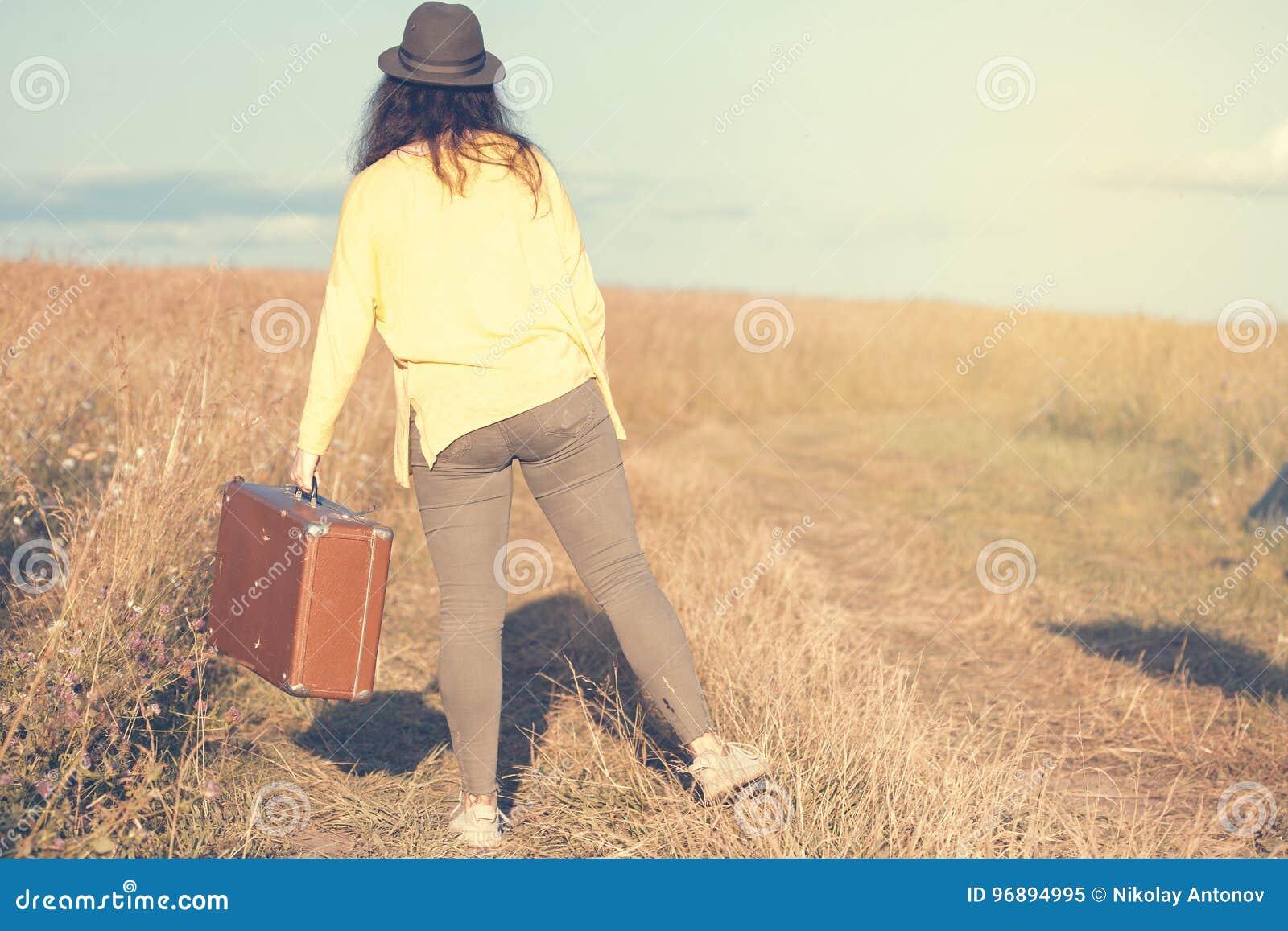 La belle jeune femme avec le chapeau noir porte la valise brune de vintage dans la route de champ pendant le coucher du soleil d