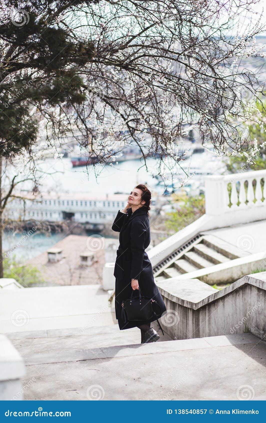La belle jeune femme dans le manteau de laine sombre dans la rue chronomètrent au printemps Fleurs de fleurs d amande, manteau à