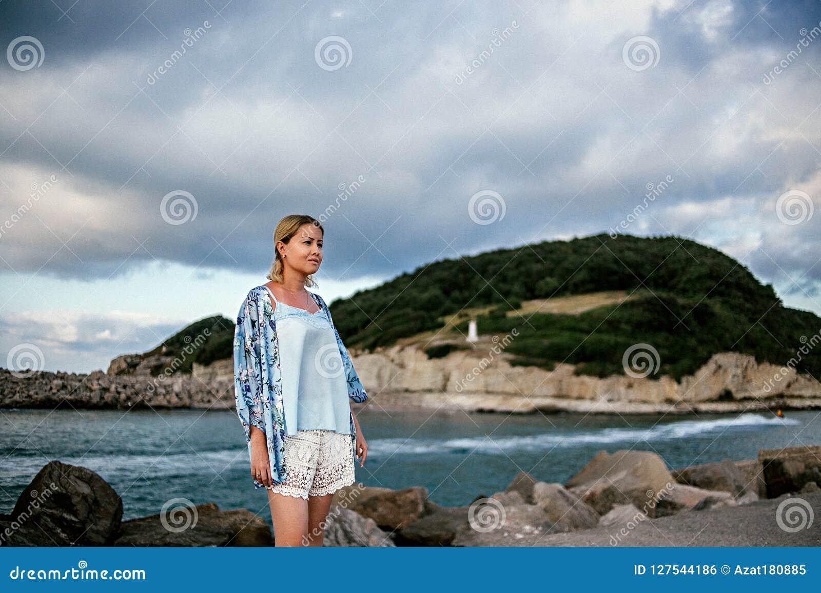 La belle jeune femme en été léger vêtx par la mer dans les montagnes de fond et le beau ciel