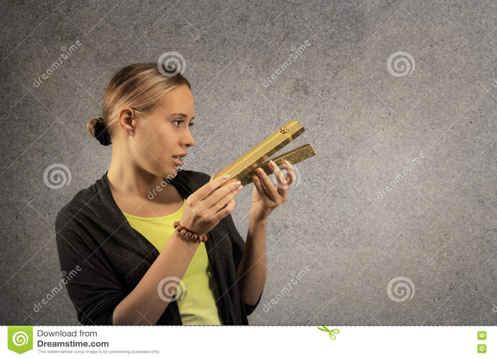 La belle jeune femme gaie en tissus occasionnels se demandent ce qui est boîte actuelle d or intérieure dans des ses mains