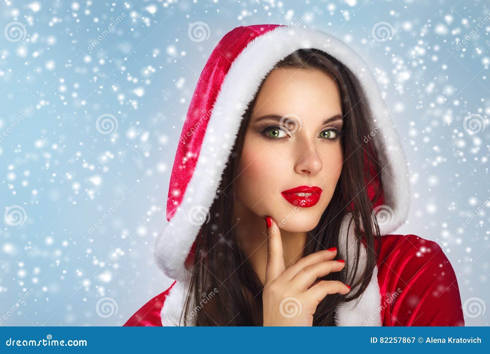 La belle jeune femme heureuse en Santa Claus vêtx au-dessus du fond de Noël Femme de sourire au-dessus du fond blanc Verticale de