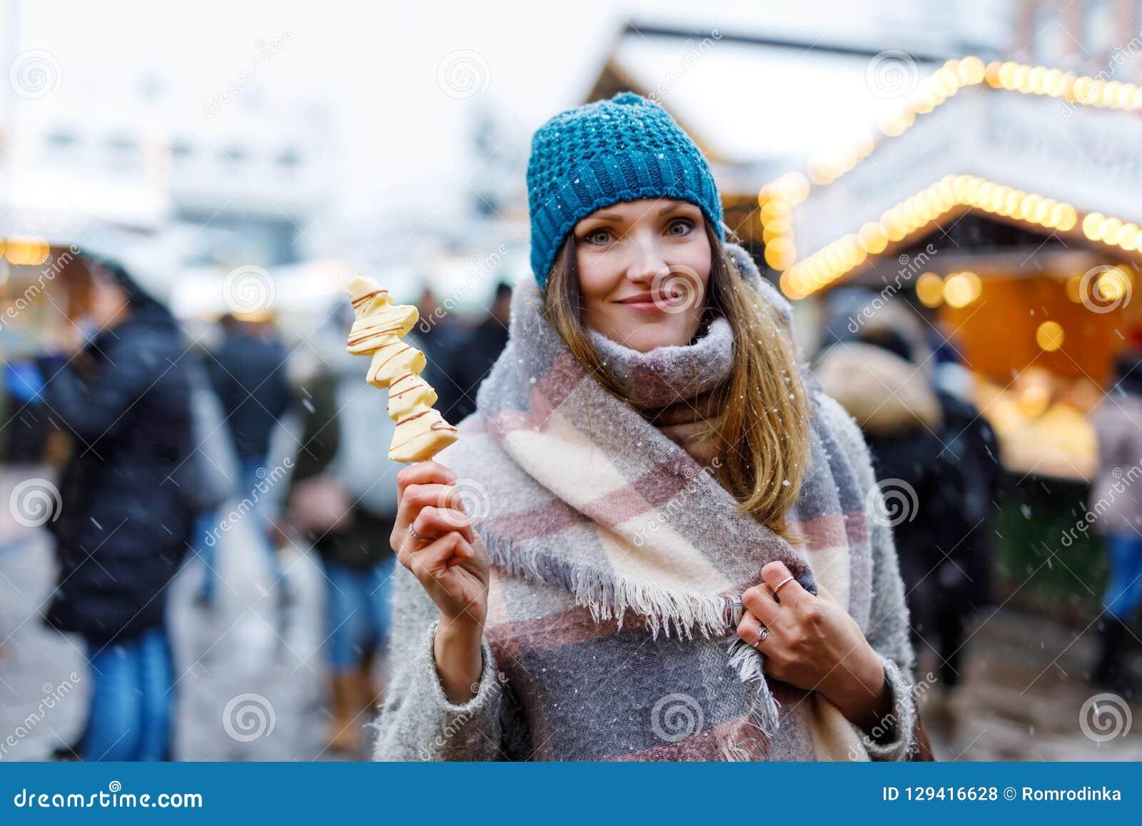 La belle jeune femme mangeant du chocolat blanc a couvert des fruits sur la brochette sur le marché allemand traditionnel de Noël