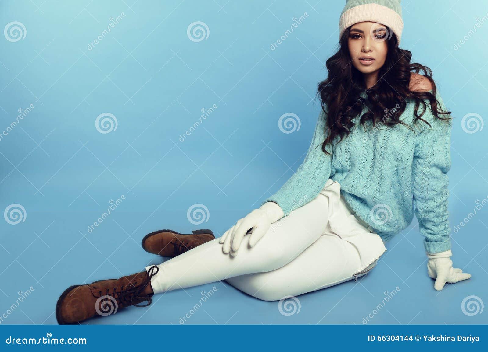La belle jeune fille avec les cheveux bouclés foncés porte les vêtements chauds confortables