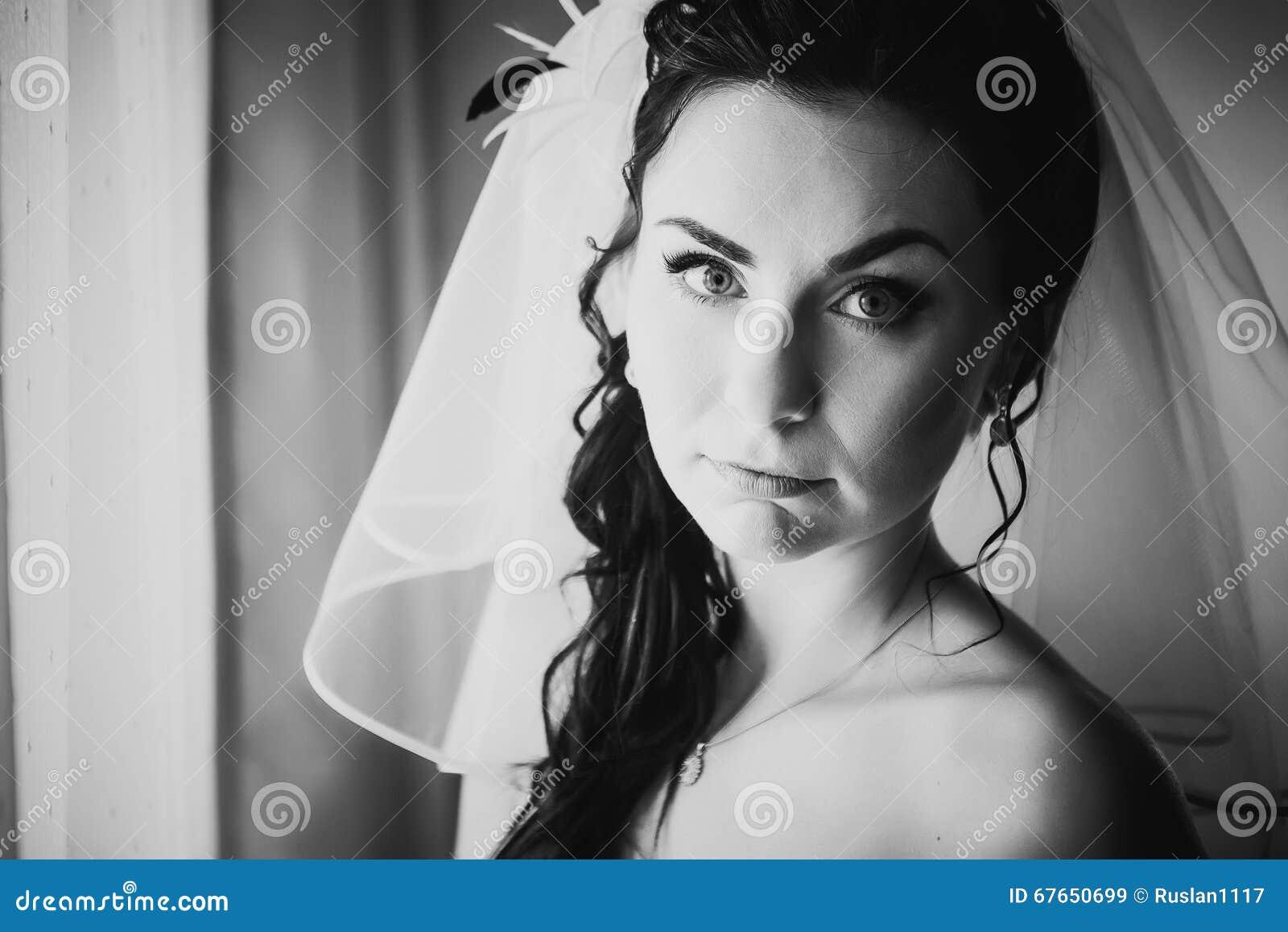 La belle jeune jeune mariée de photographie blanche noire coûte au sujet de la fenêtre élégante