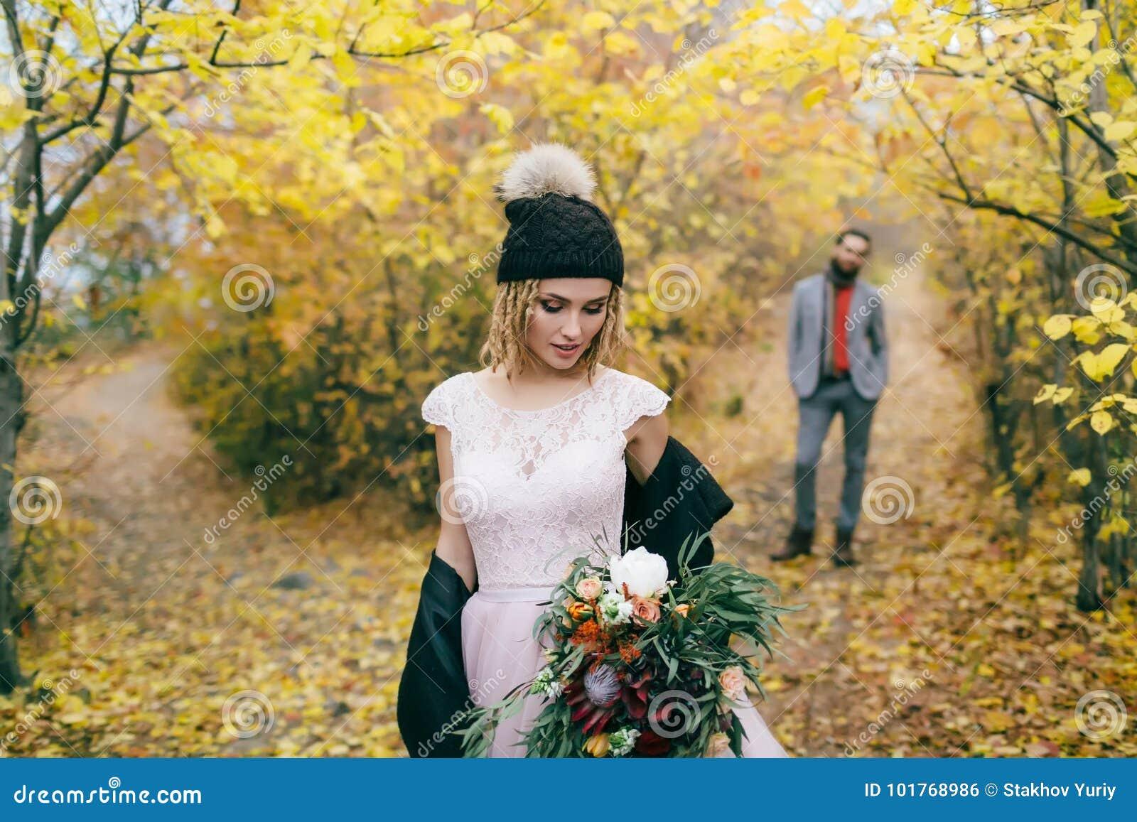 La belle jeune mariée dans un chapeau tricoté avec un pompon posent dans la forêt d automne sur le fond brouillé du ` s de marié