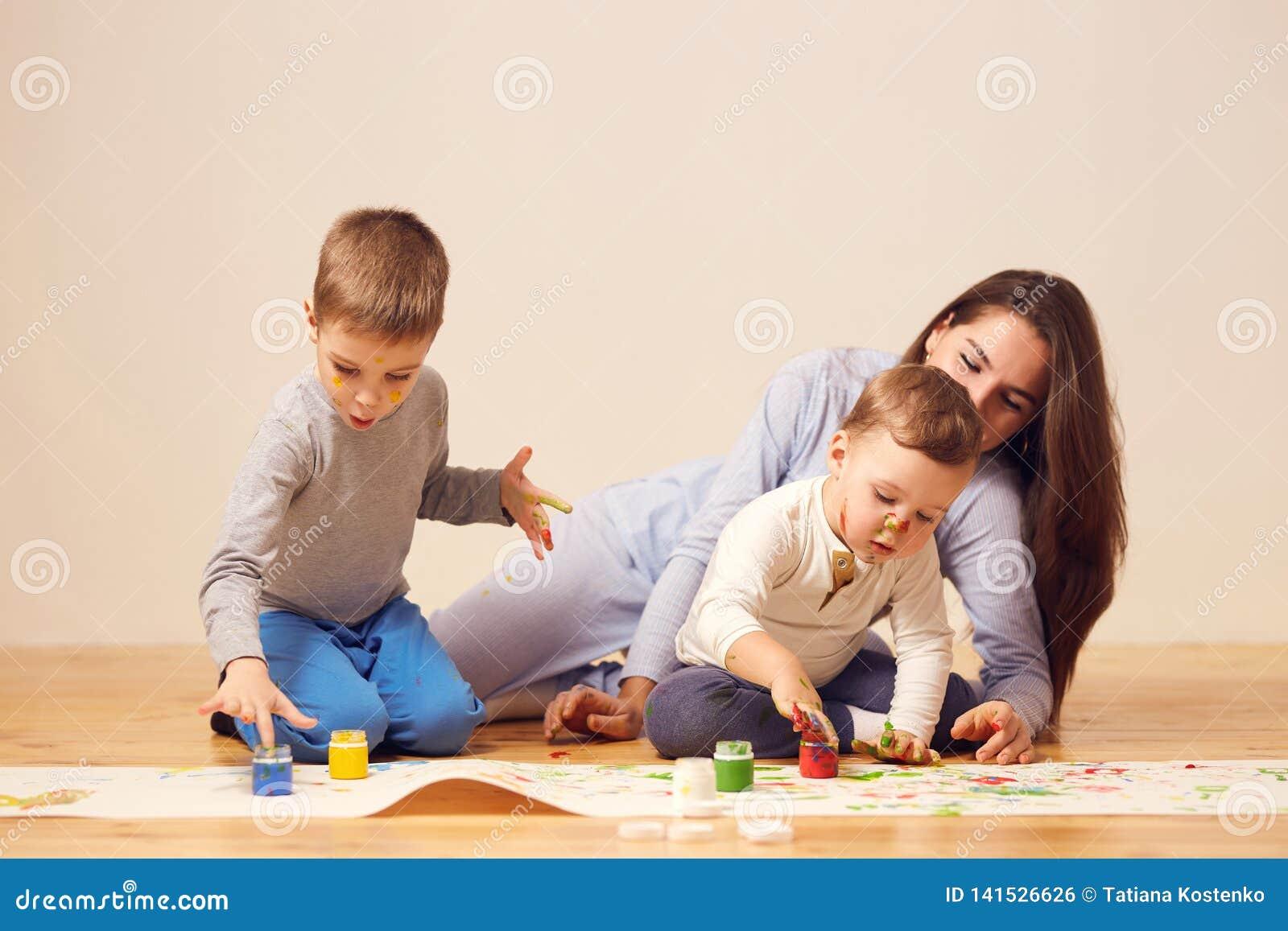La belle mère heureuse et ses deux petits les fils habillés dans des vêtements à la maison s asseyent sur le plancher en bois dan