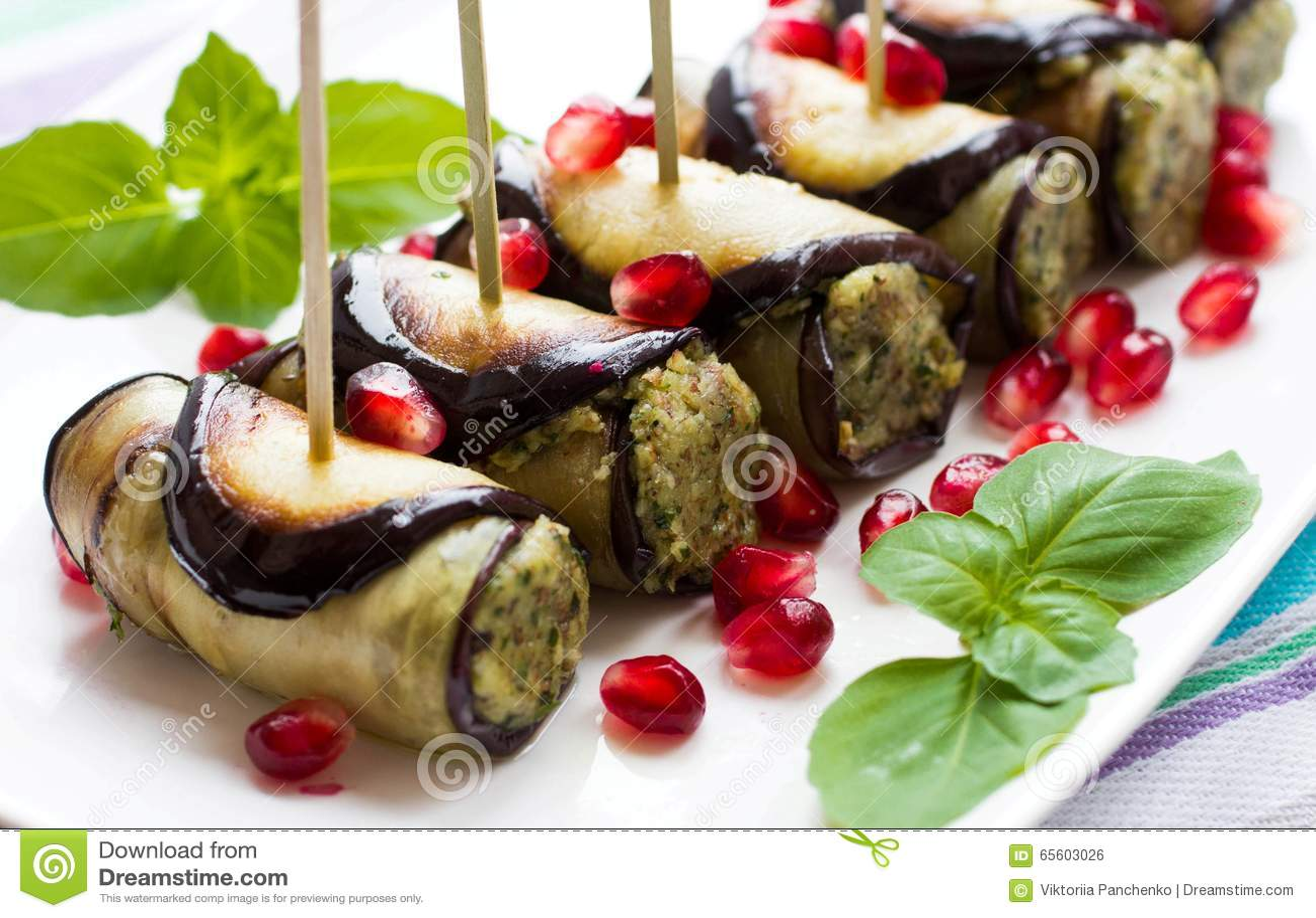 La berenjena rueda con las nueces Arrancador delicioso de berenjenas fritas con las nueces, las hierbas y las semillas de la gran