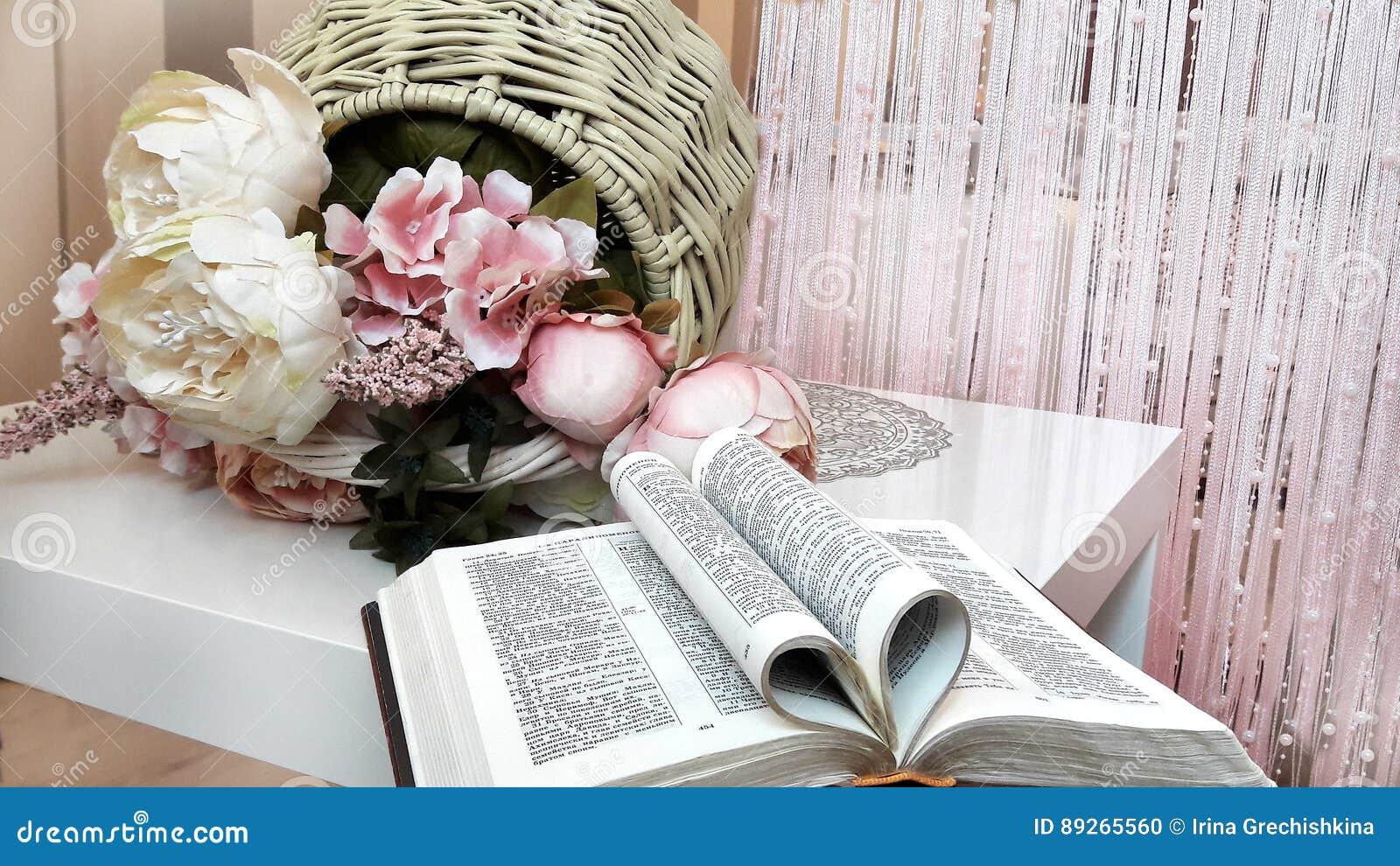 La Biblia Abierta Y Una Cesta De Flores En La Tabla Foto De Archivo