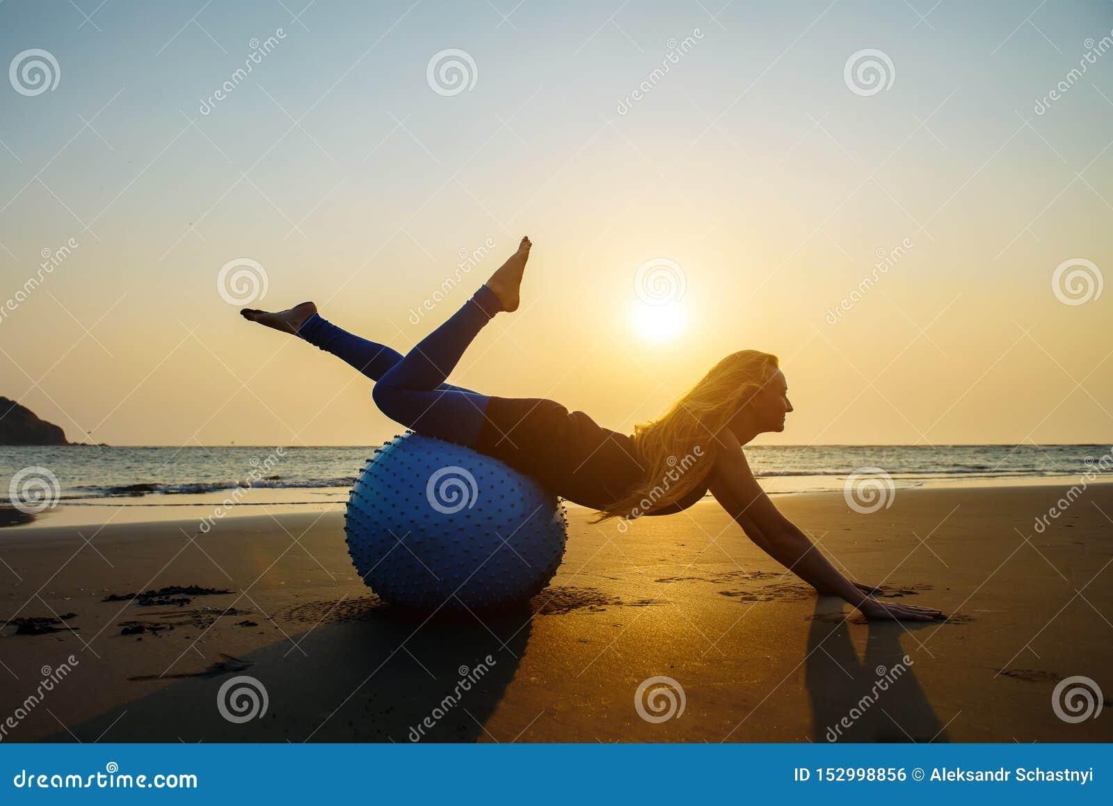 La Bionda Con Capelli Lunghi Fa Pilates Sulla Spiaggia ...