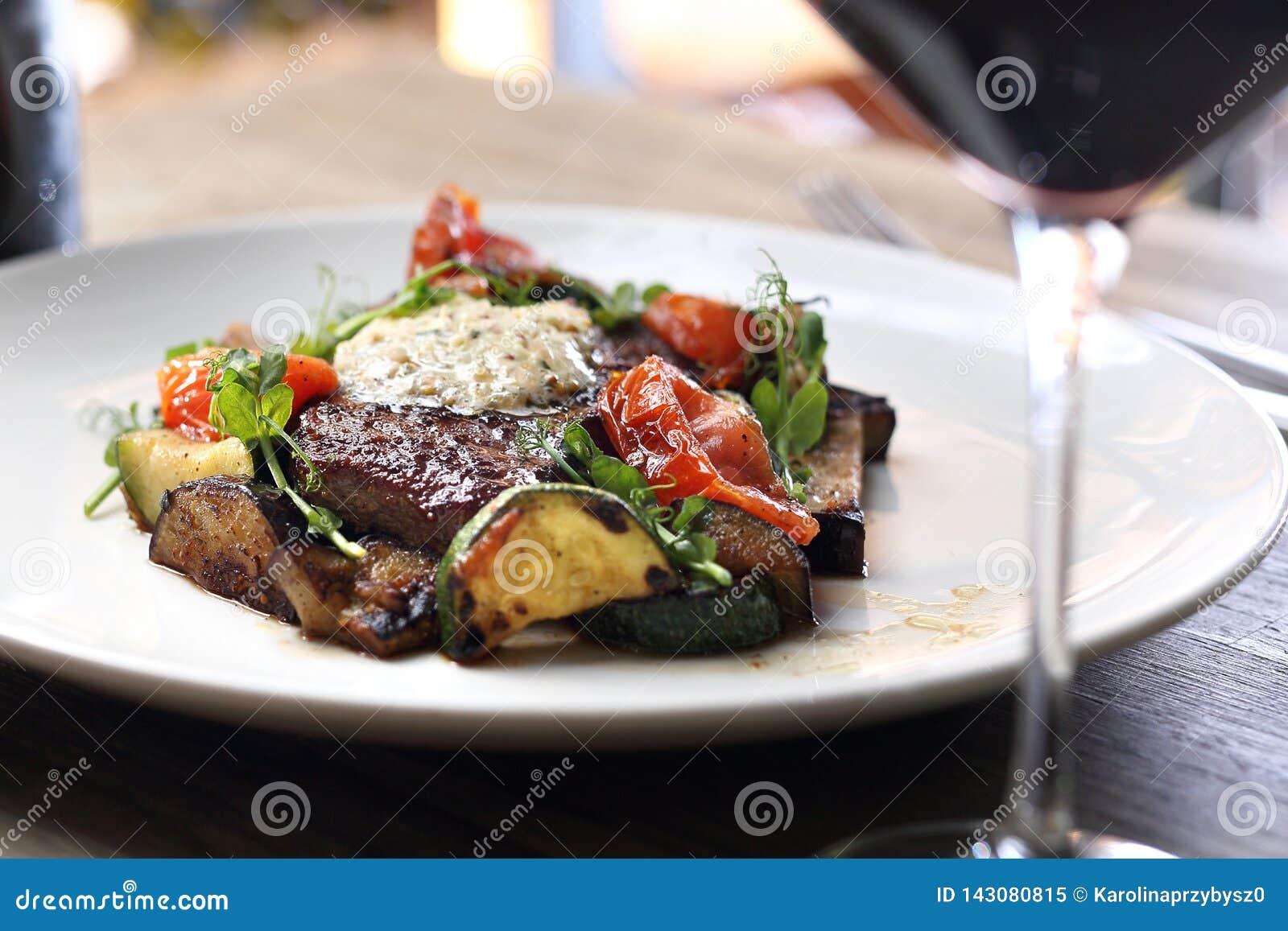 La bistecca di entrecôte con il burro di erba e le verdure arrostite è servito con un vetro di vino rosso