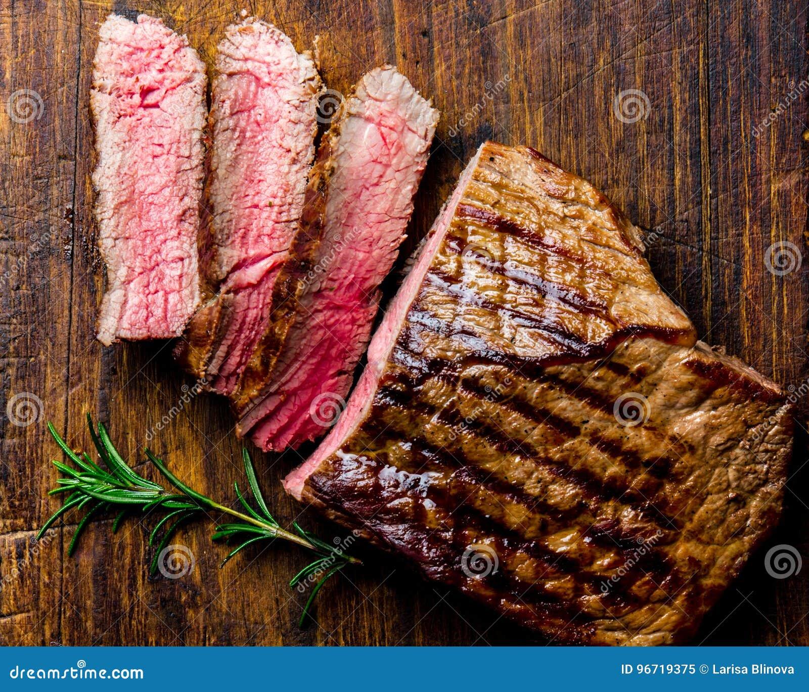 La bistecca di manzo rara media arrostita affettata è servito sul barbecue del bordo di legno, filetto di manzo della carne del b