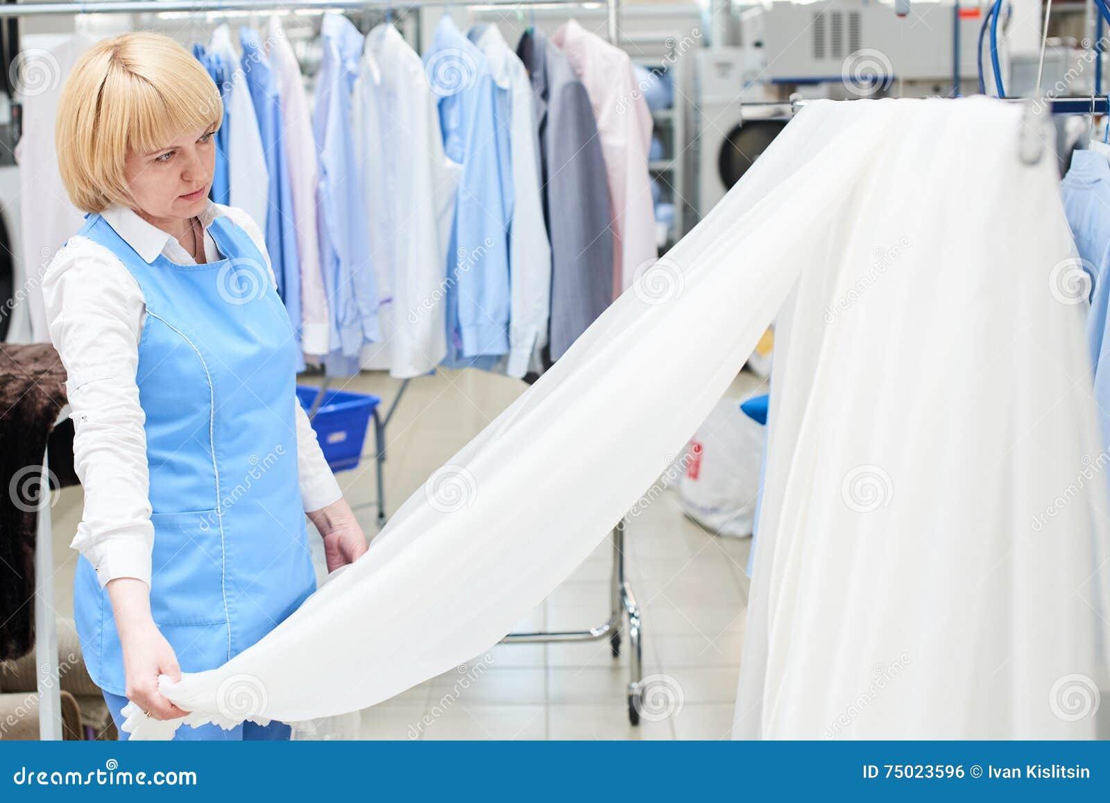 La blanchisserie de ouvrière de fille regarde et vérifie de Tulle blanc et pur