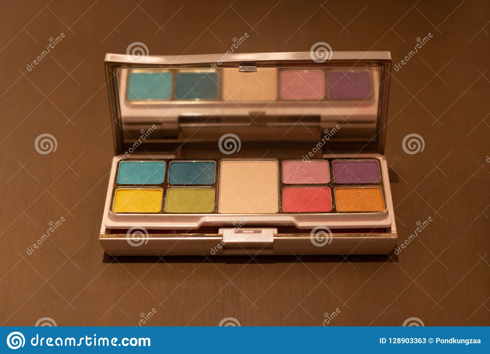 La boîte cosmétique de poudre a placé beaucoup la couleur sur la table en bois