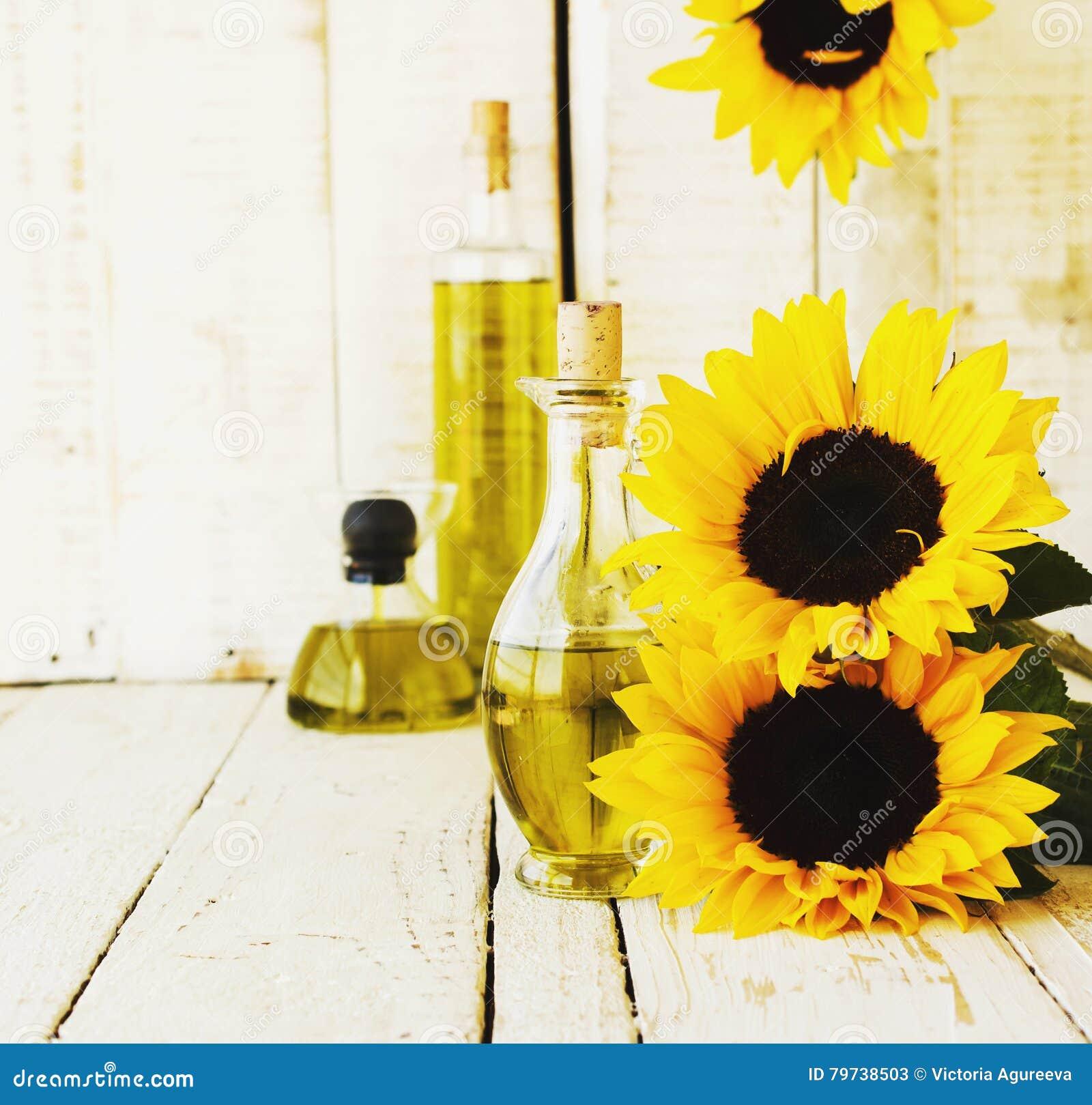 La botella con aceite florece el girasol, foco selectivo