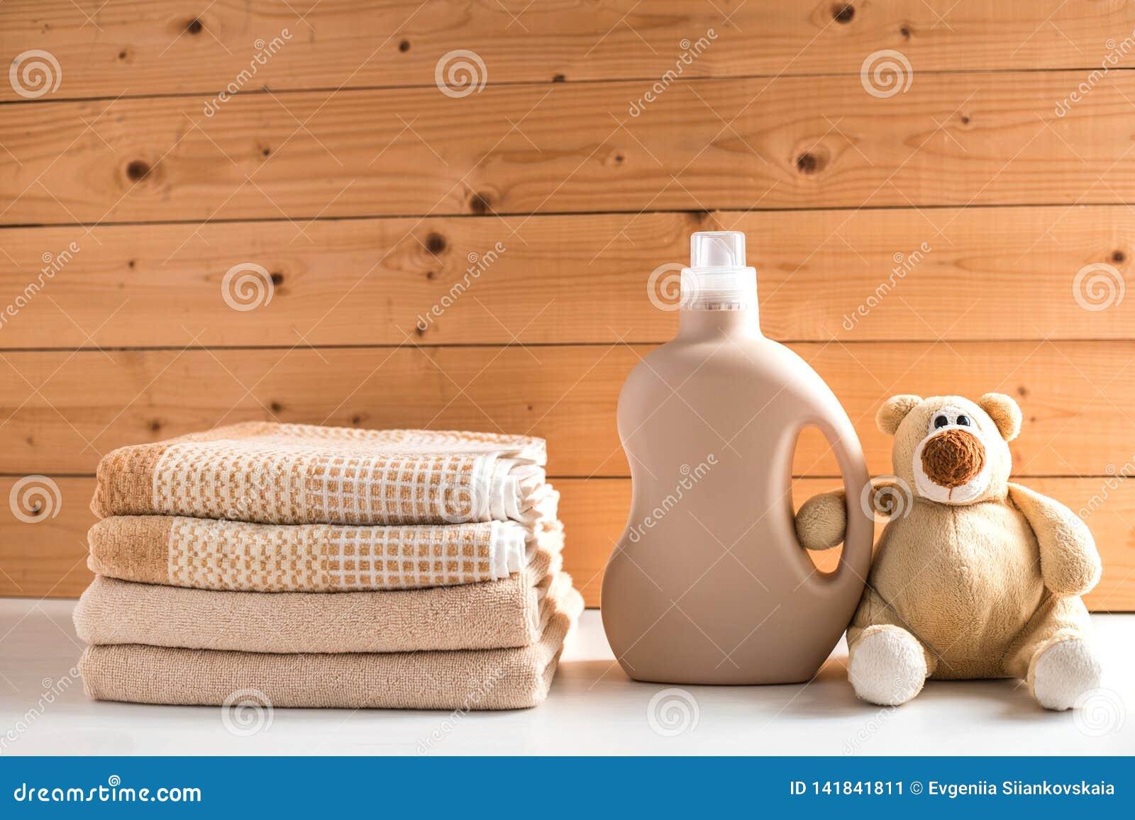 La bottiglia del detersivo vicino ad un mucchio degli asciugamani