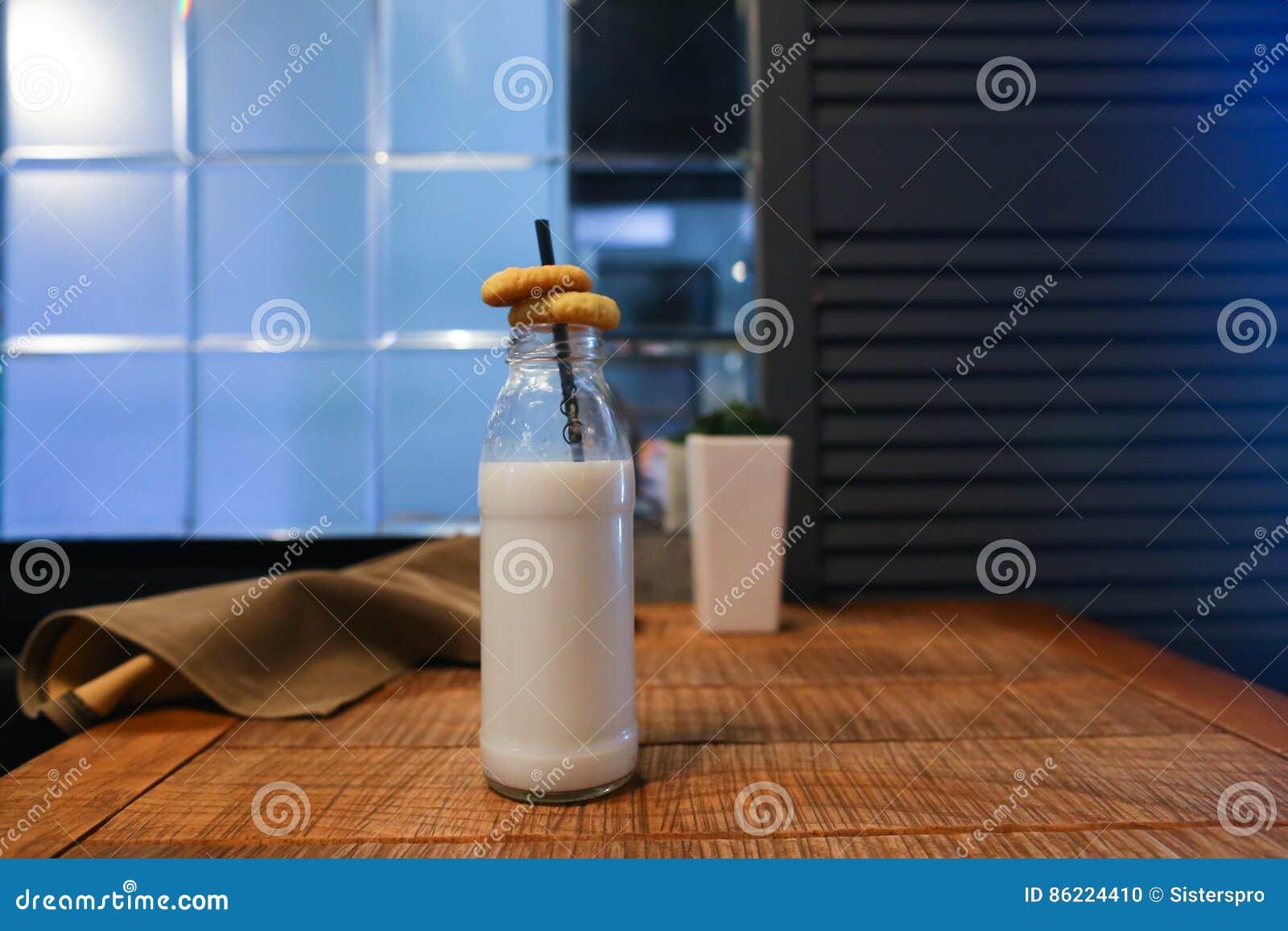 La bouteille en verre de lait la fleur dans le vase et le marais drapent sur table ag photo - La bouteille sur la table ...