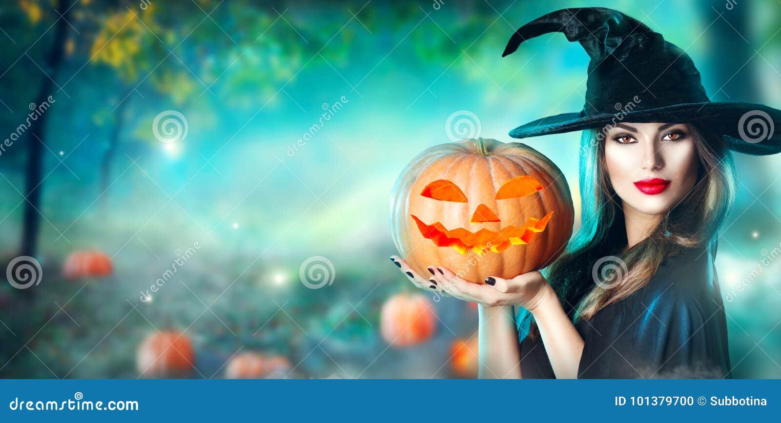La bruja de Halloween con una calabaza y una magia talladas se enciende en un bosque