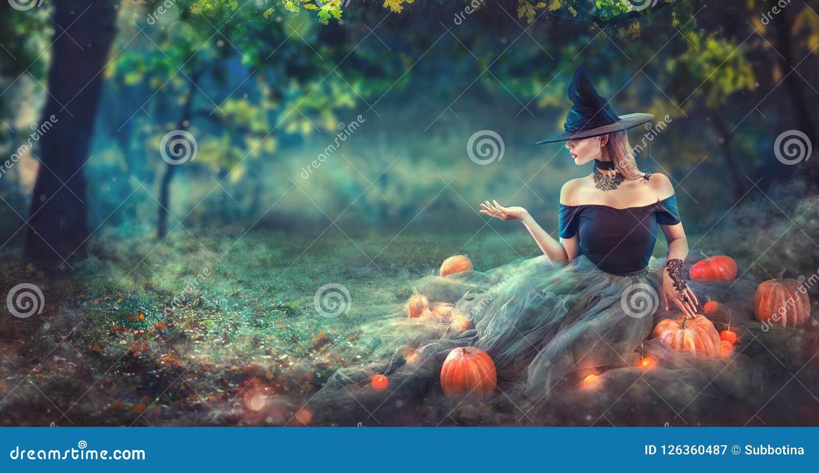 La bruja de Halloween con una calabaza y una magia talladas se enciende en un bosque oscuro en la noche Mujer joven hermosa en tr