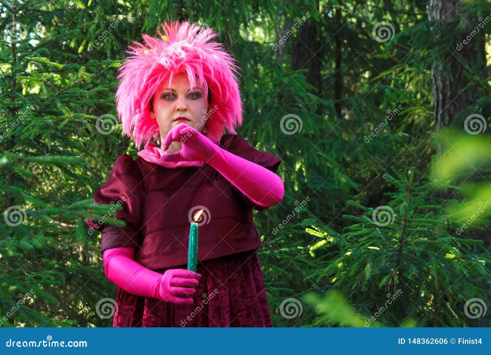 La bruja del bosque en ropa púrpura conjura entre el bosque con las velas Foto vertical