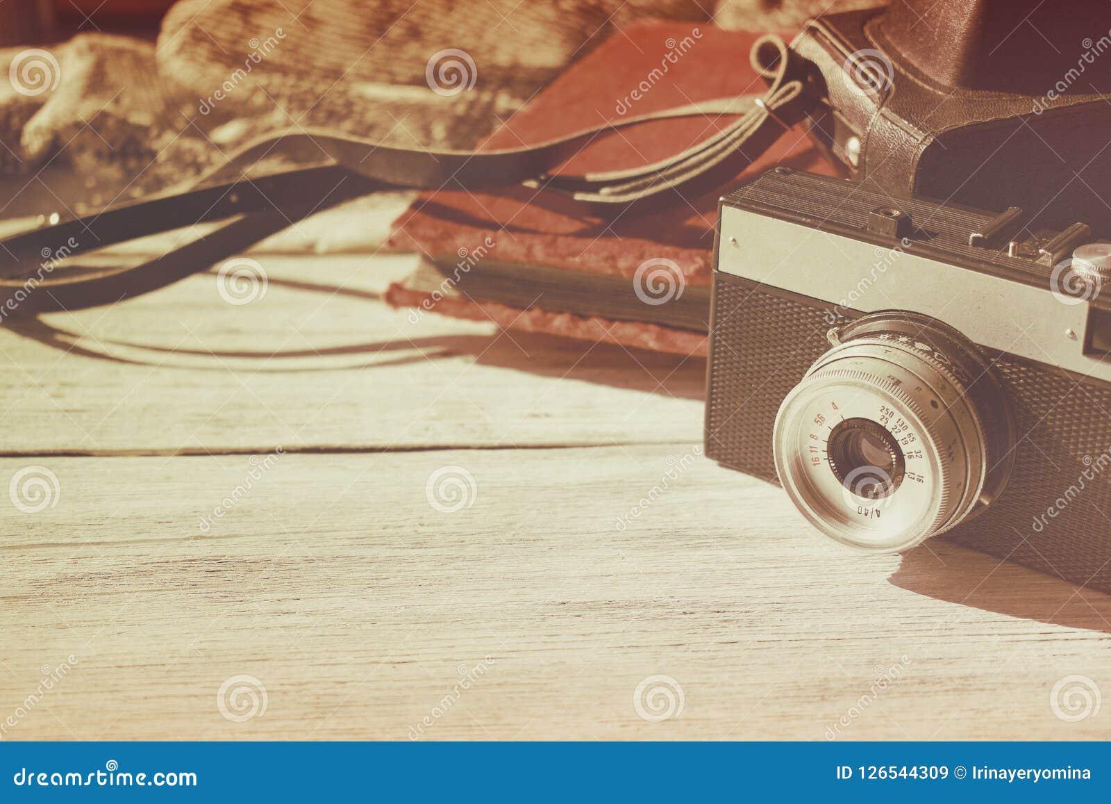 La cámara vieja retra con la foto de cuero negra del vintage del caso y del terciopelo en el fondo de madera blanco copia el espa