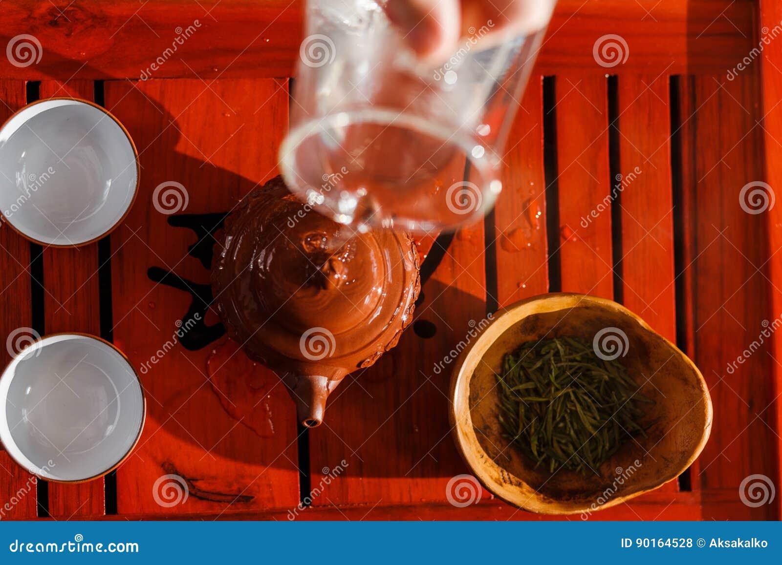 La cérémonie de thé La femme rince la théière