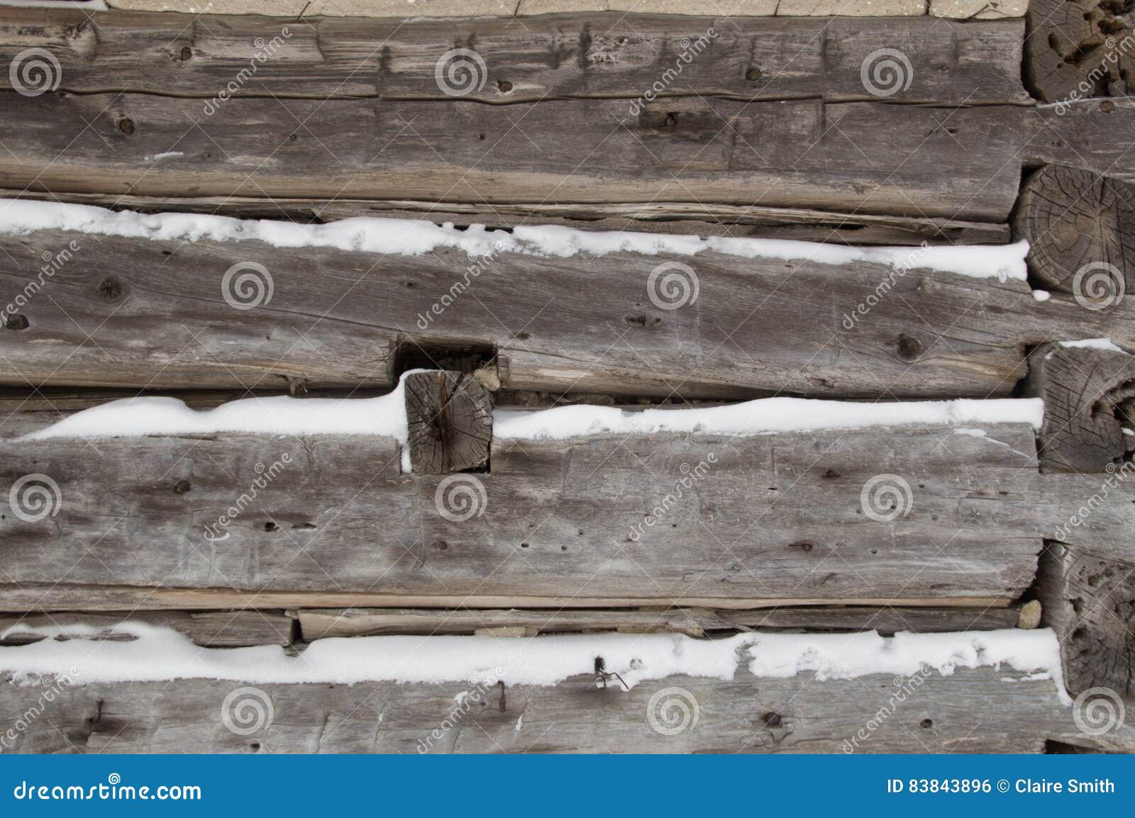 La cabaña de madera aserró registros para arrinconar el primer con nieve mientras tanto