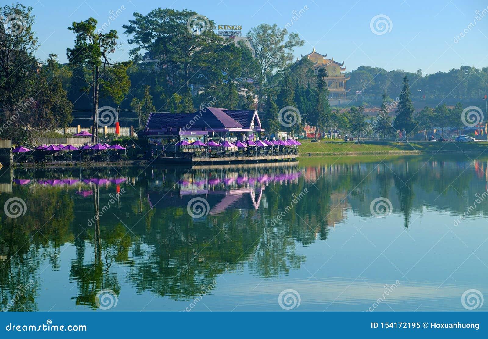 La cafetería violeta de la orilla del lago, parasol refleja en centro de ciudad del lat del lago, DA