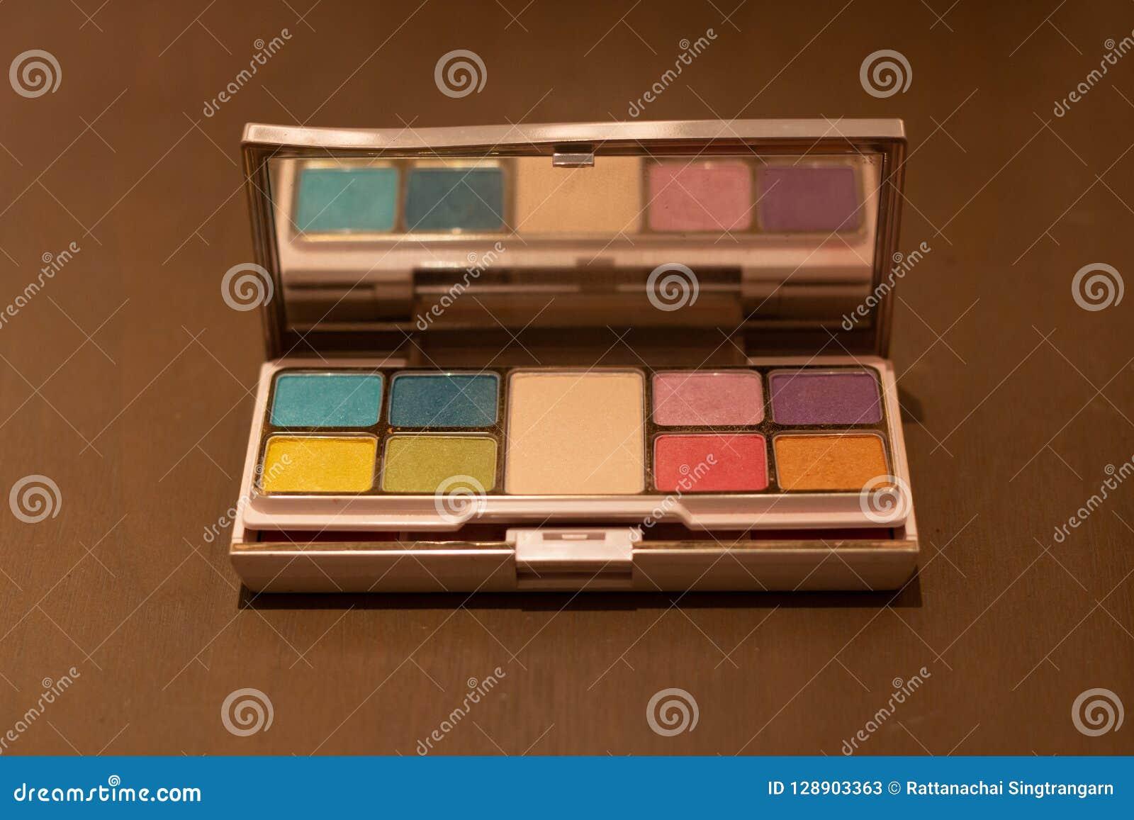 La caja cosmética del polvo fijó mucho color en la tabla de madera