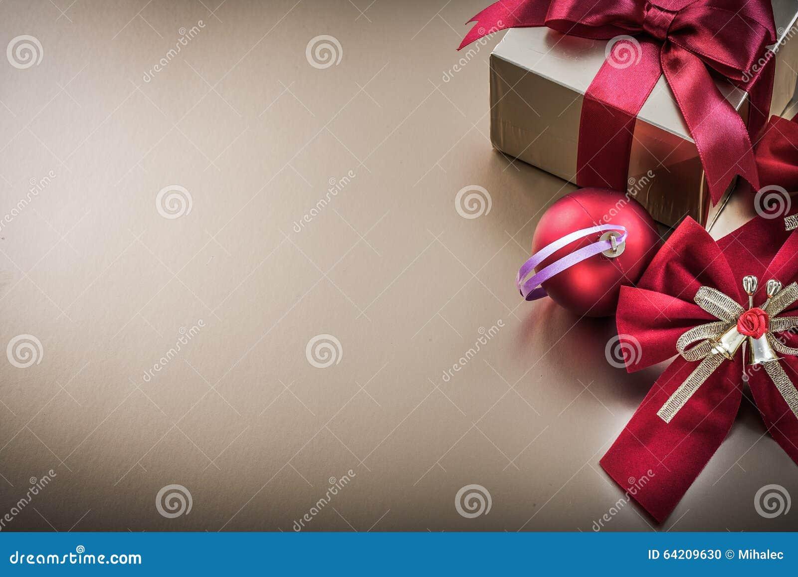 La caja de regalo de la bola de la Navidad con la cinta atada arquea