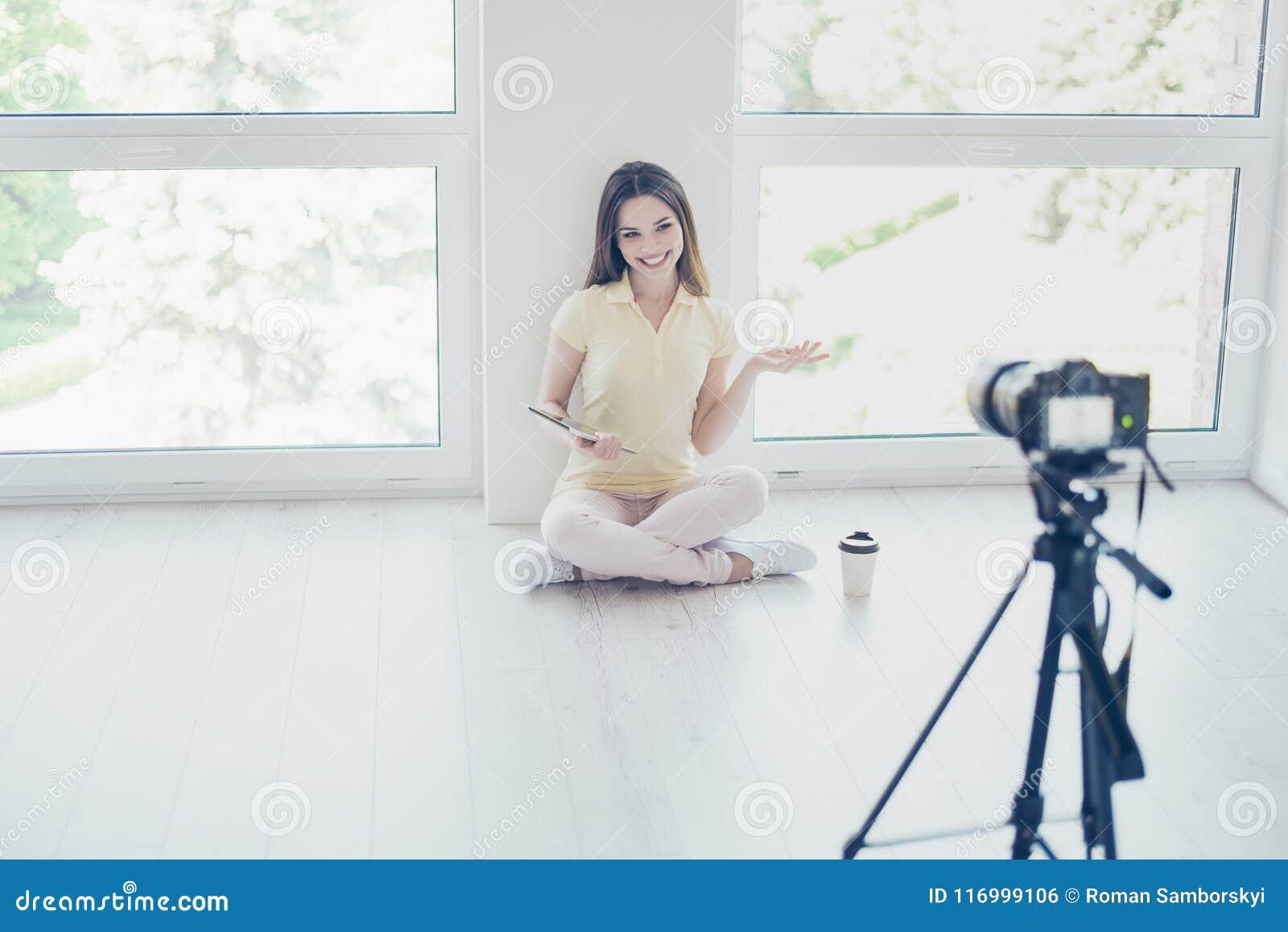 La caméra vidéo enregistre le joli blogger de fille de brune, parlant
