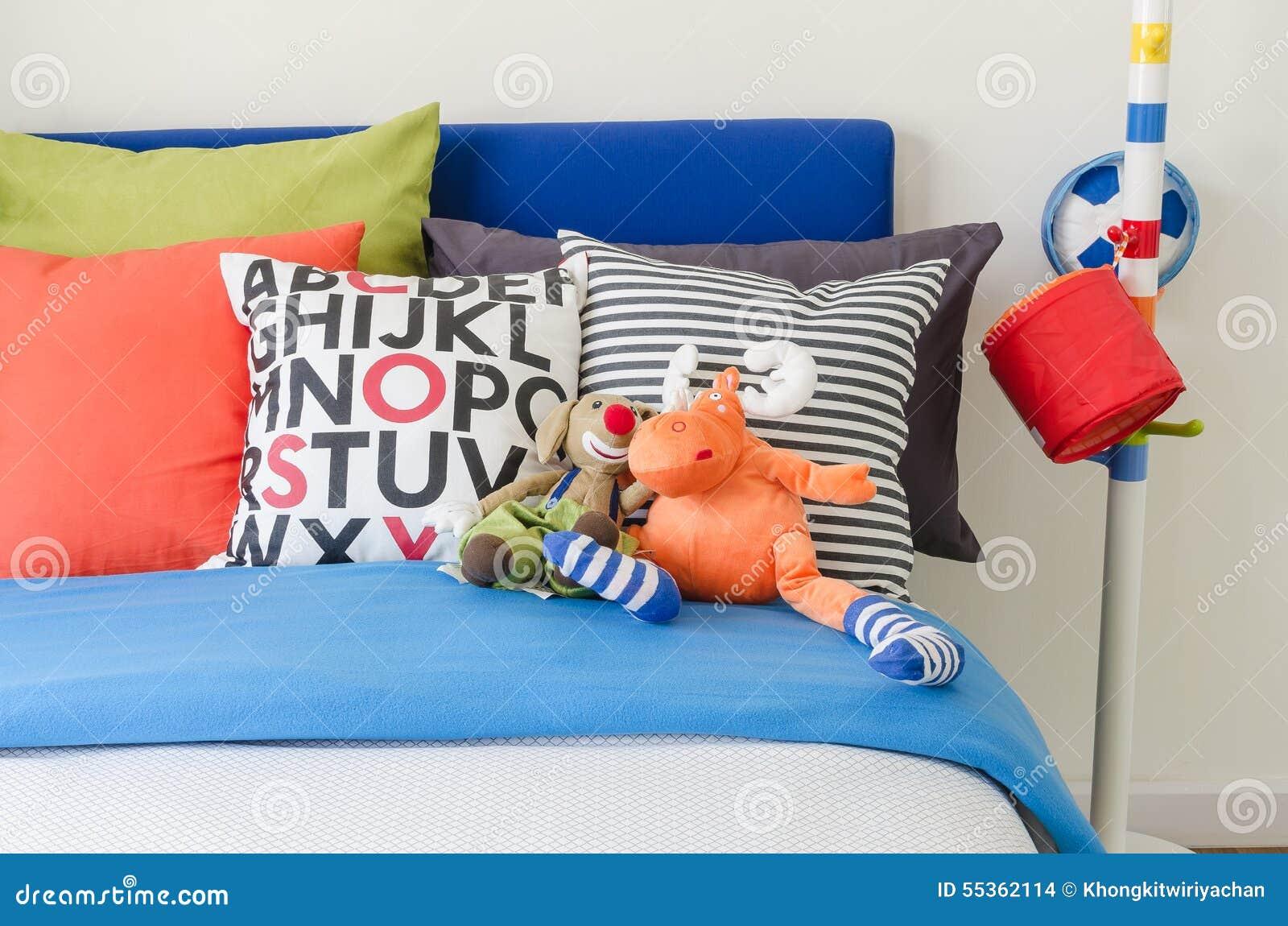 La camera da letto del bambino con i cuscini variopinti e le bambole