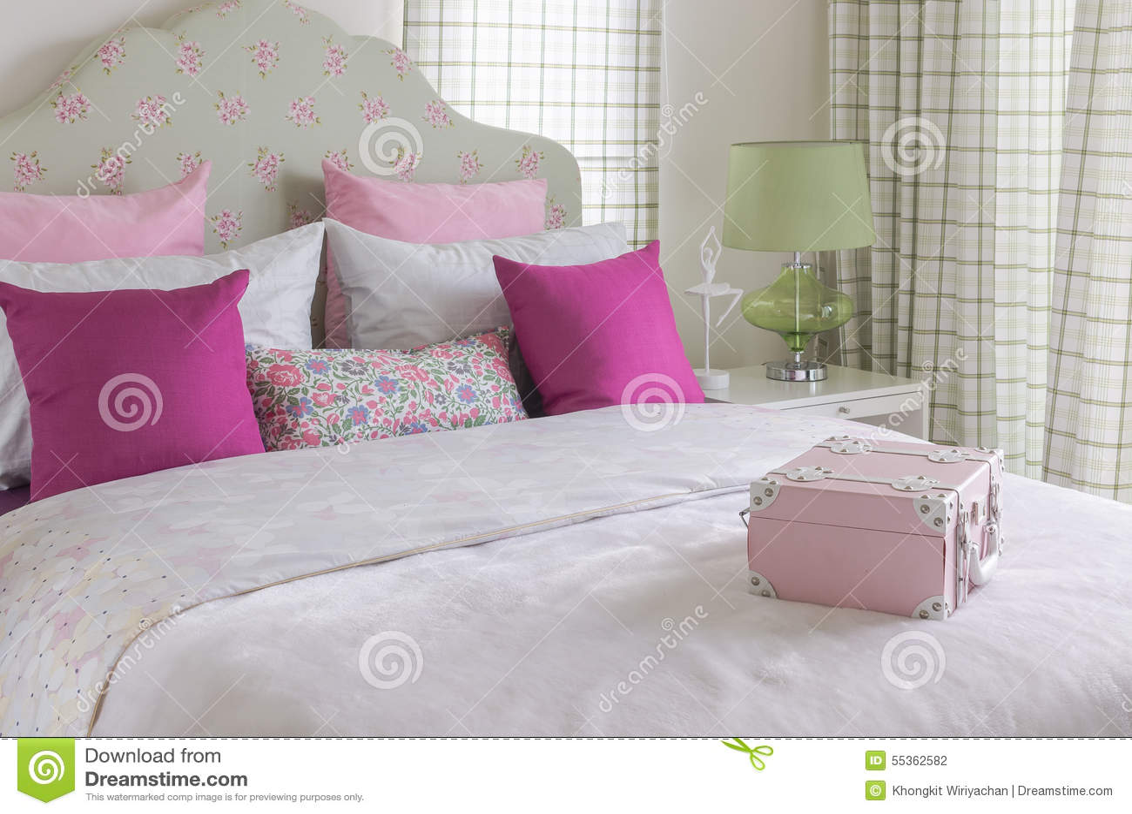 La camera da letto della ragazza con il cuscino rosa sul letto verde