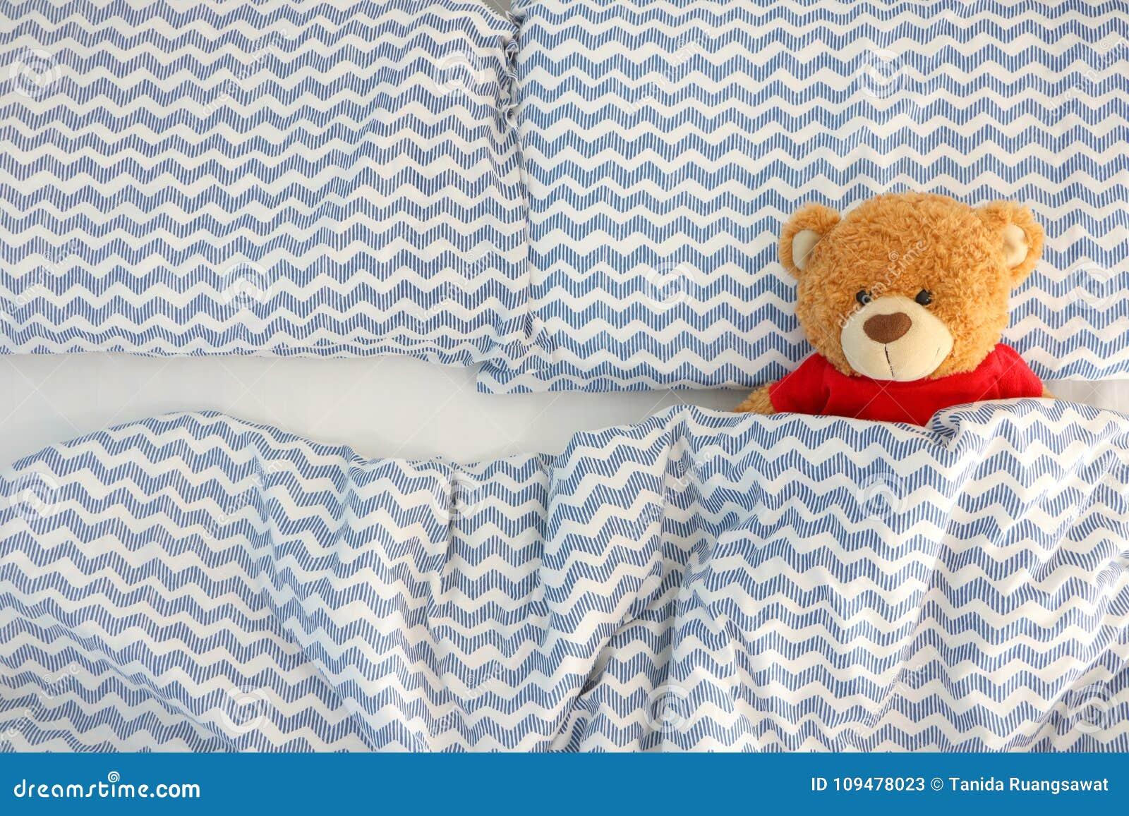 La camisa roja del solo del oso marrón desgaste de la muñeca que duerme en la cama tiene espacio en el lado izquierdo Concepto qu