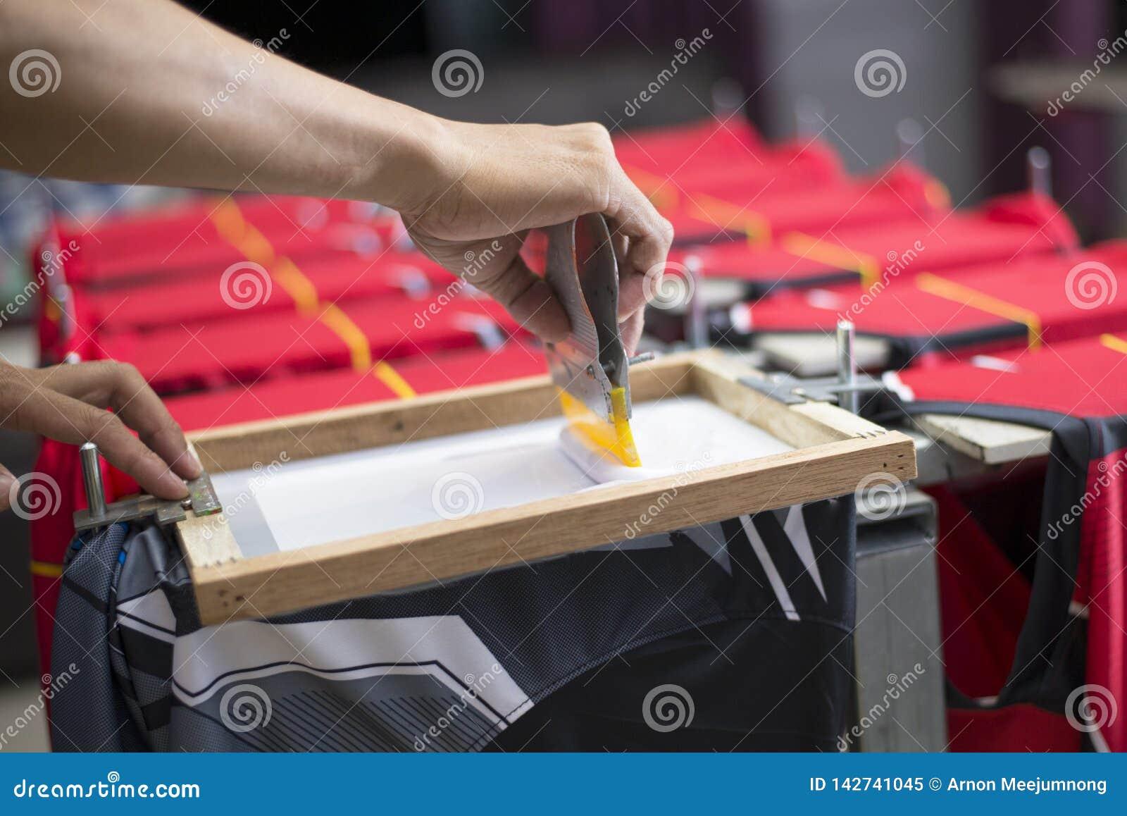 La camiseta hecha a mano de la impresión de la pantalla, trabajadores está funcionando