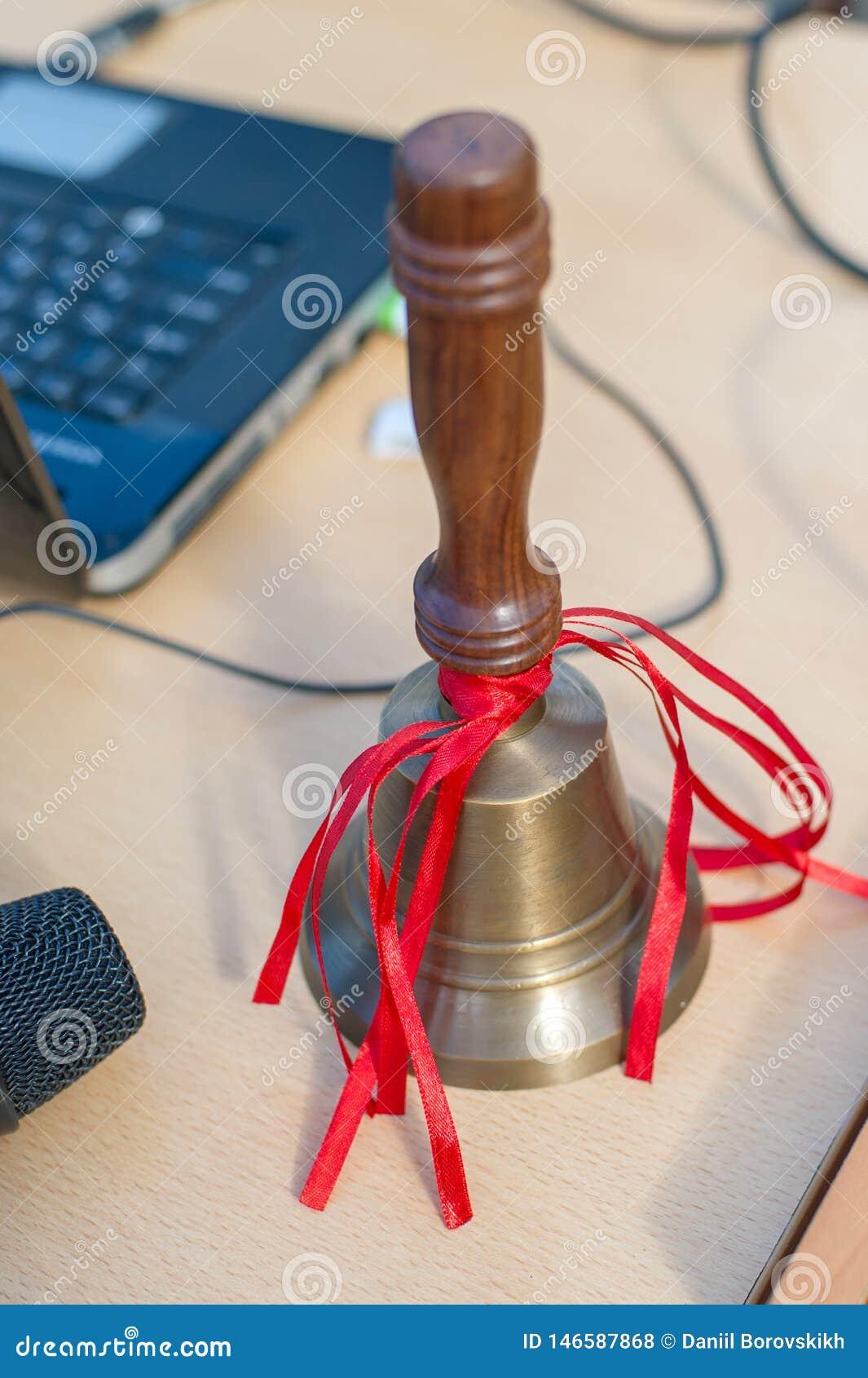 La campana de escuela en la tabla con las cintas rojas