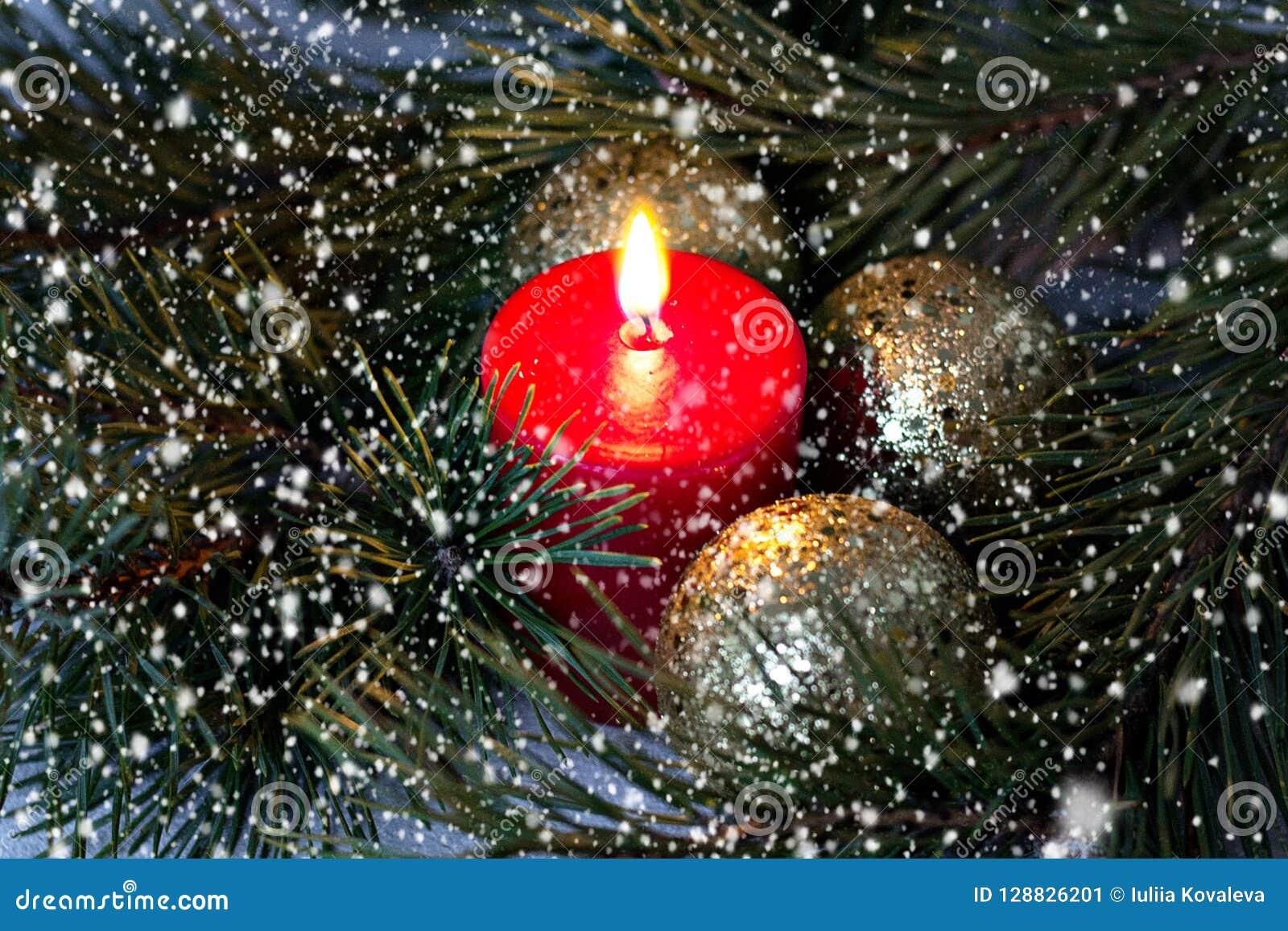 La candela bruciante rossa e le palle dorate di Natale con un abete si ramificano sotto neve andante