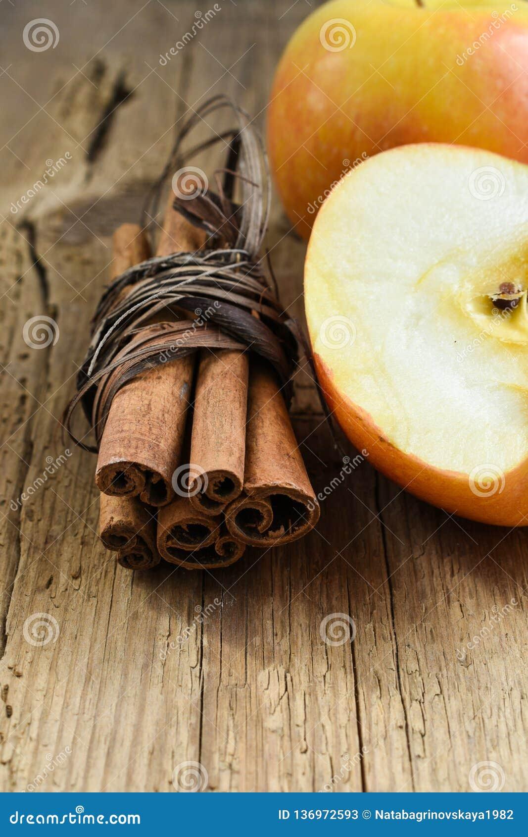 La cannelle colle avec la pomme sur la table en bois