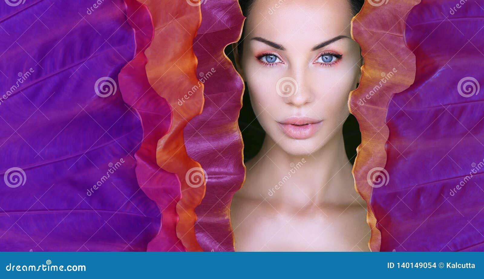 La cara de la mujer rodeada por el marco colorido ultravioleta Cara hermosa de la mujer con maquillaje natural en una hoja de neó