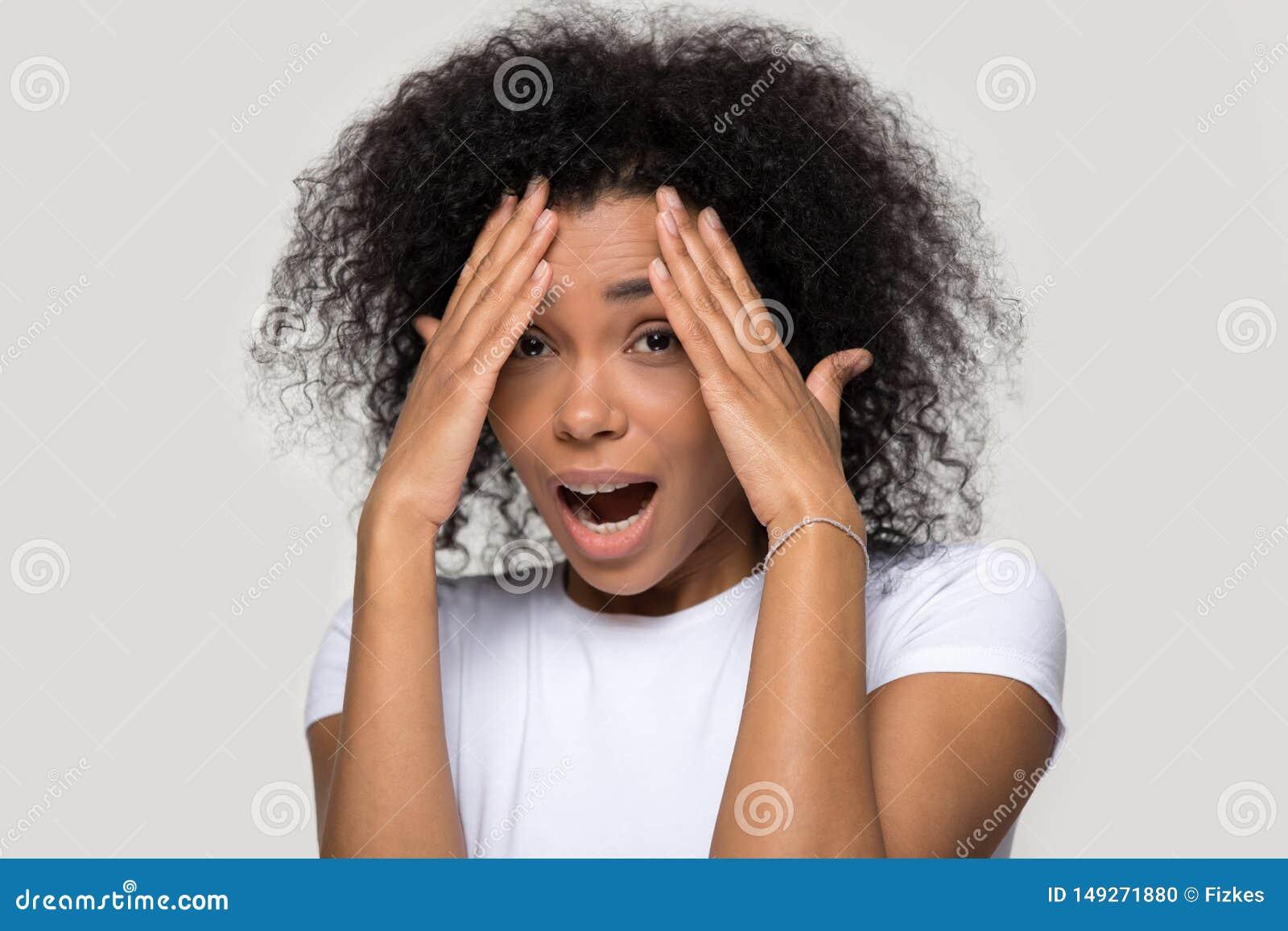 La cara femenina africana de la cubierta con la mano siente el tiro asustado del estudio