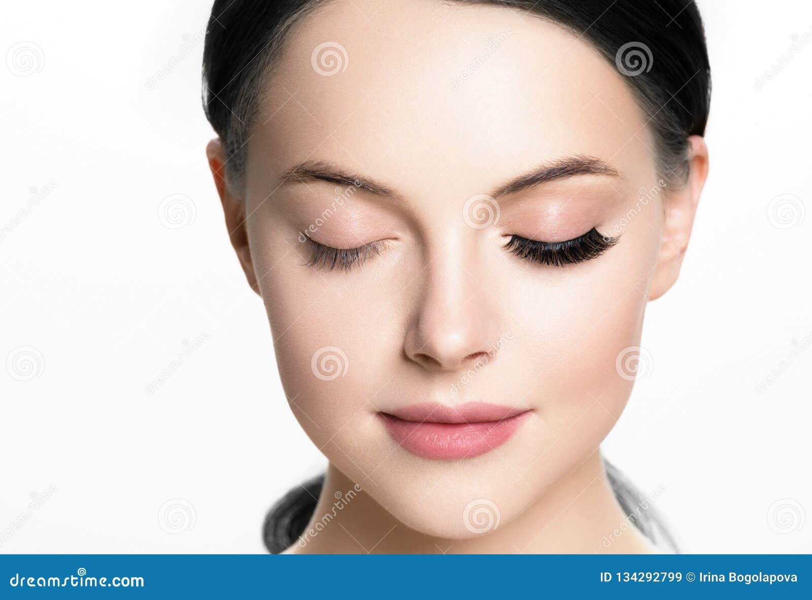 La cara hermosa de la mujer con las pestañas azota la extensión antes y después de que el maquillaje natural de la piel sana de l