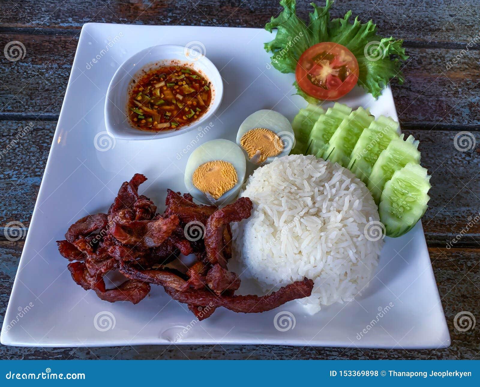 La carne di maiale profonda infornata in piatto bianco è stata servita con la salsa del riso, dell uovo sodo e di refrigerazione
