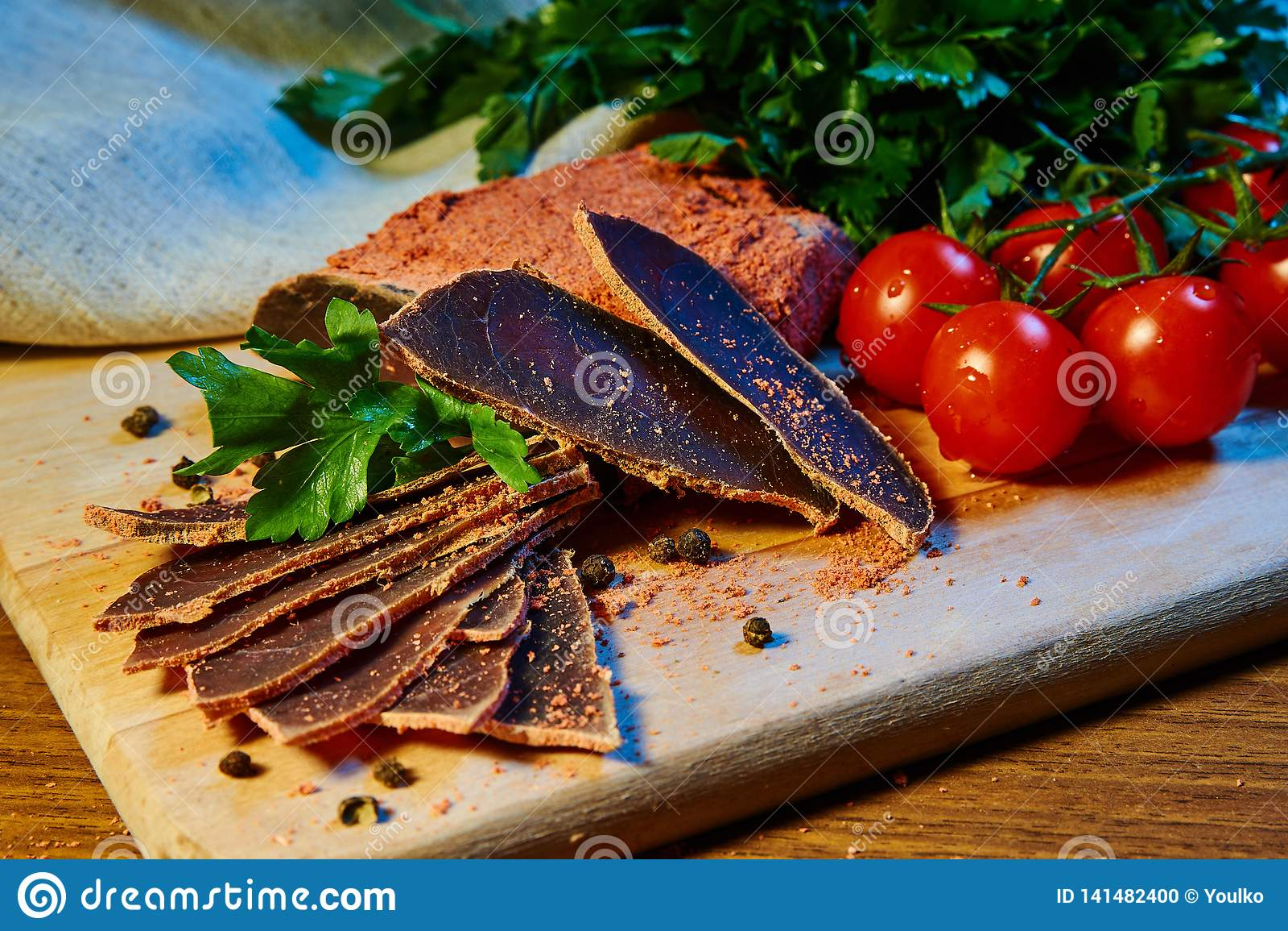 La carne secada, basturma miente en un tablero de madera con las alcaparras y las especias perejil fresco y tomates de cereza roj