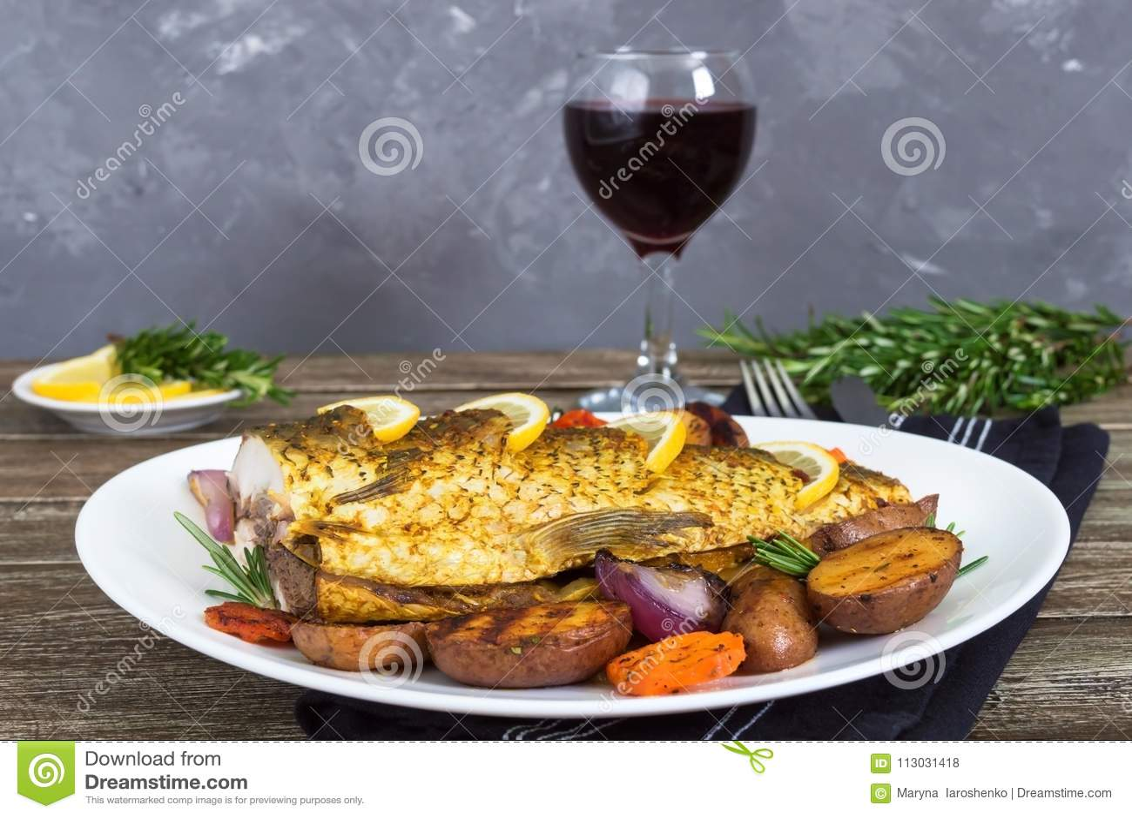 La carpa cocida con las verduras asó a la parrilla en una placa blanca