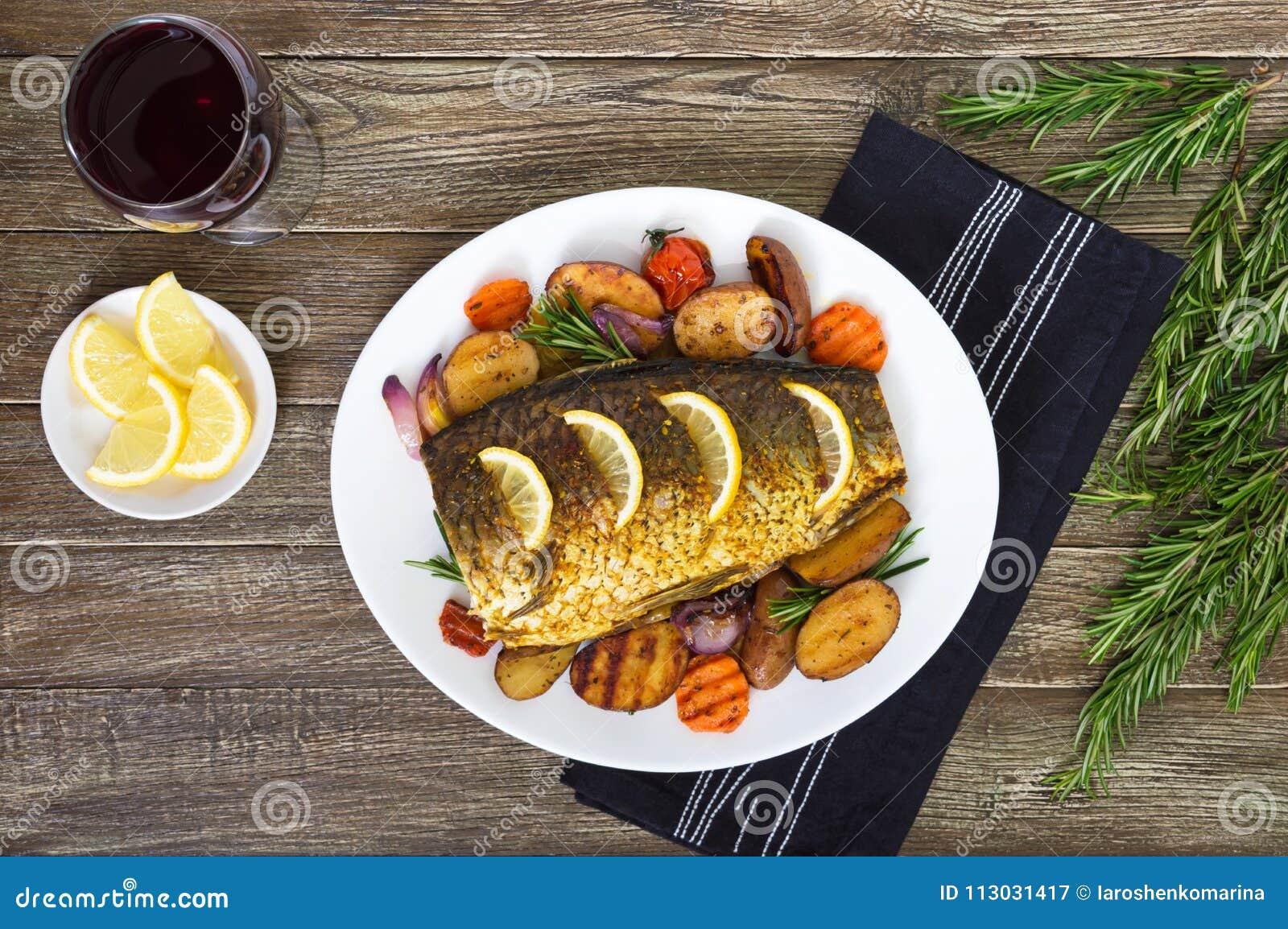 La carpa cocida con las verduras asó a la parrilla en una placa blanca y un vidrio de vino rojo en un fondo de madera
